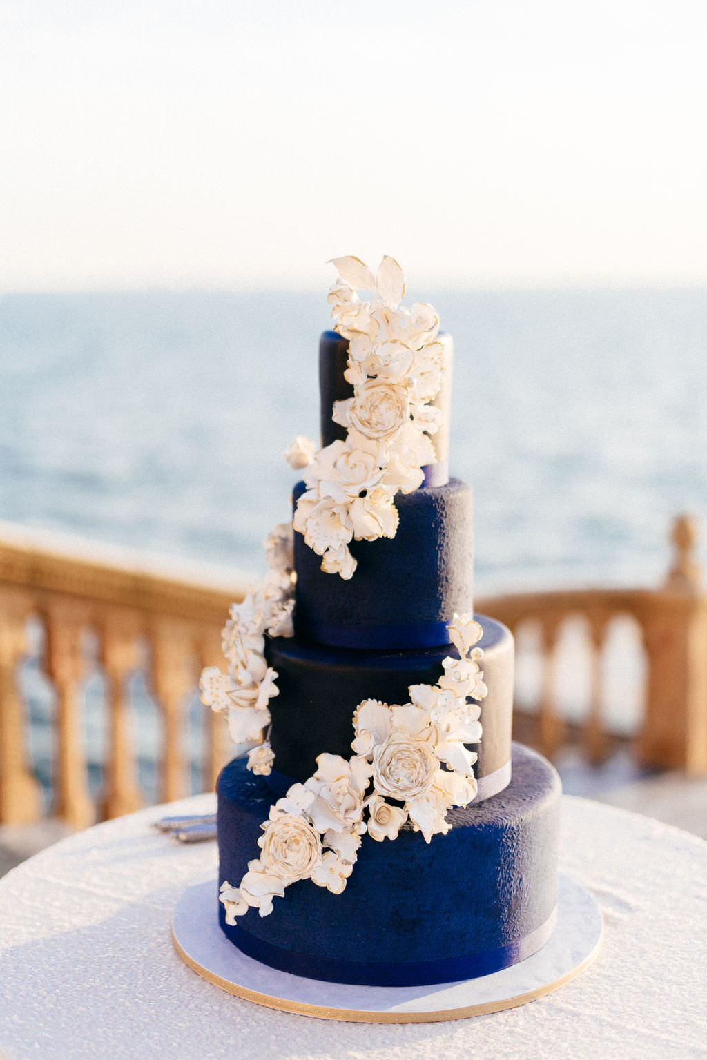 INSTAGRAM Four Tier Navy Blue Wedding Cake with Cascading White and Gold Sugar Flowers