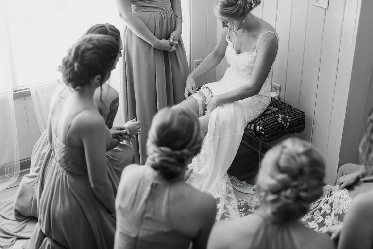 St. Petersburg Bride Putting on Lace Garter Wearing Lace V Neckline with Spaghetti Straps Classic Wedding Dress with Bridesmaids Portrait | Tampa Bay Wedding Photographer Kera Photography | Wedding Dress Shop Truly Forever Bridal