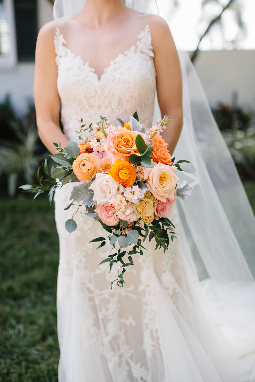 INSTAGRAM Romantic Whimsical Bride in Lace Watters with Illusion Neckline Wedding Dress Holding Blush Pink and Orange Roses, Dusty Miller Leaves, Greenery Floral Bridal Bouquet | Tampa Bay Wedding Florist Bruce Wayne Florals