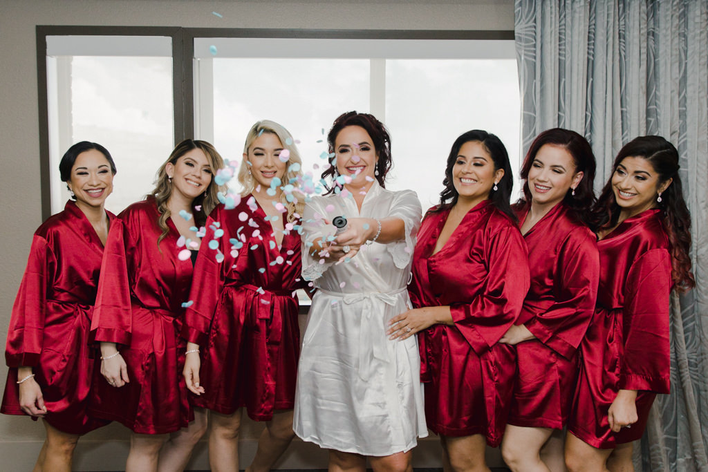 Fun Bride And Bridesmaids In Satin Red Robes With Confetti Popper Wedding Portrait Marry Me Tampa Bay Local Real Wedding Inspiration Vendor Recommendation Reviews