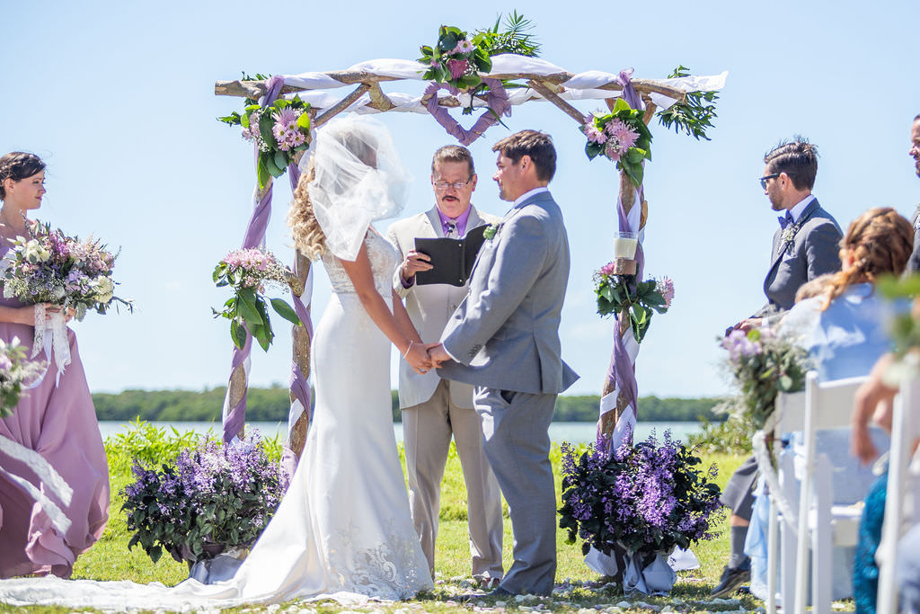 Easter Spring Theme Wedding, Bride and Groom Exchanging Vows During Waterfront Ceremony Under Birchwood Arch with Purple, Lilac, White Floral Arrangements and Draping