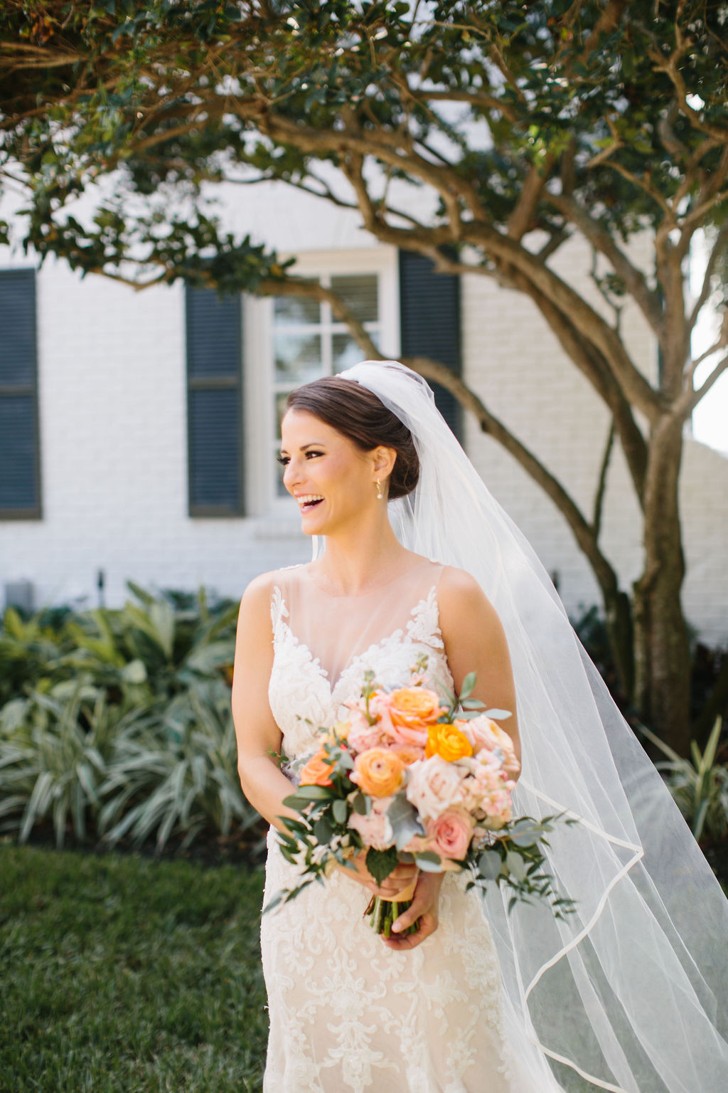 Romantic Florida Bride Beauty Portrait Wearing Lace and Illusion Neckline Watters Wedding Dress with Full Length Veil Holding Whimsical Orange and Blush Pink Roses, Dusty Miller Leaves, Eucalyptus Floral Bridal Bouquet | Tampa Bay Wedding Florist Bruce Wayne Florals | St. Pete Wedding Hair and Makeup Femme Akoi Beauty Studio
