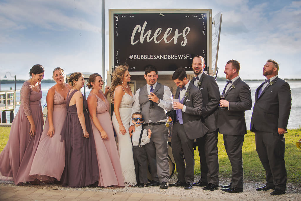 Easter Spring Tampa Bay Bride, Groom and Wedding Party Waterfront Portrait , Bridesmaids in Mix and Match Purple, Lavender and Blush Pink Dresses, Groomsmen in Gray Suits with Purple Vests and Bowties with Fun Unique Beverage Cart Get Cozy Bubbles and Brew Cart