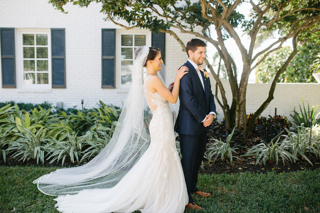 Fun Bride and Groom First Look Portrait, Bride in Romantic Lace and Illusion Watters Fit and Flare Wedding Dress with Full Length Veil | Tampa Bay Wedding Hair and Makeup Femme Akoi Beauty Studio