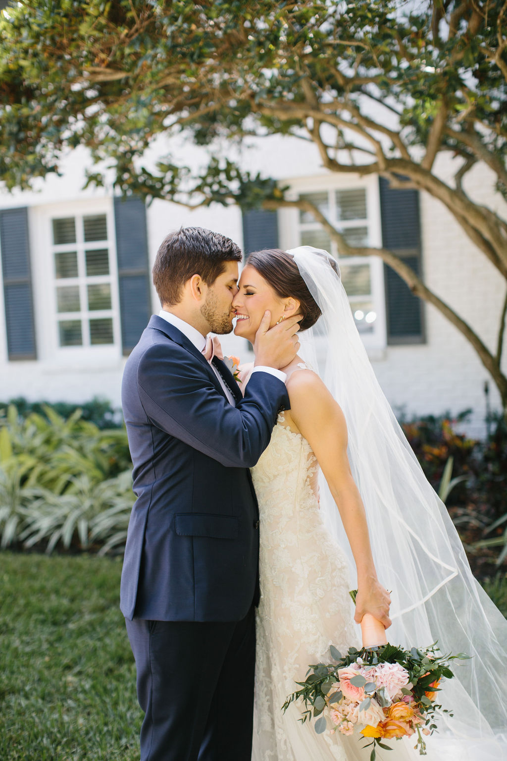 Romantic Bride and Groom Portrait, Bride Wearing Lace Watters Wedding Dress Holding Whimsical Blush Pink and Orange Roses with Greenery Floral Bouquet, Groom in Blue Suit | Tampa Bay Wedding Hair and Makeup Femme Akoi Beauty Studio | St. Pete Wedding Florist Bruce Wayne Florals