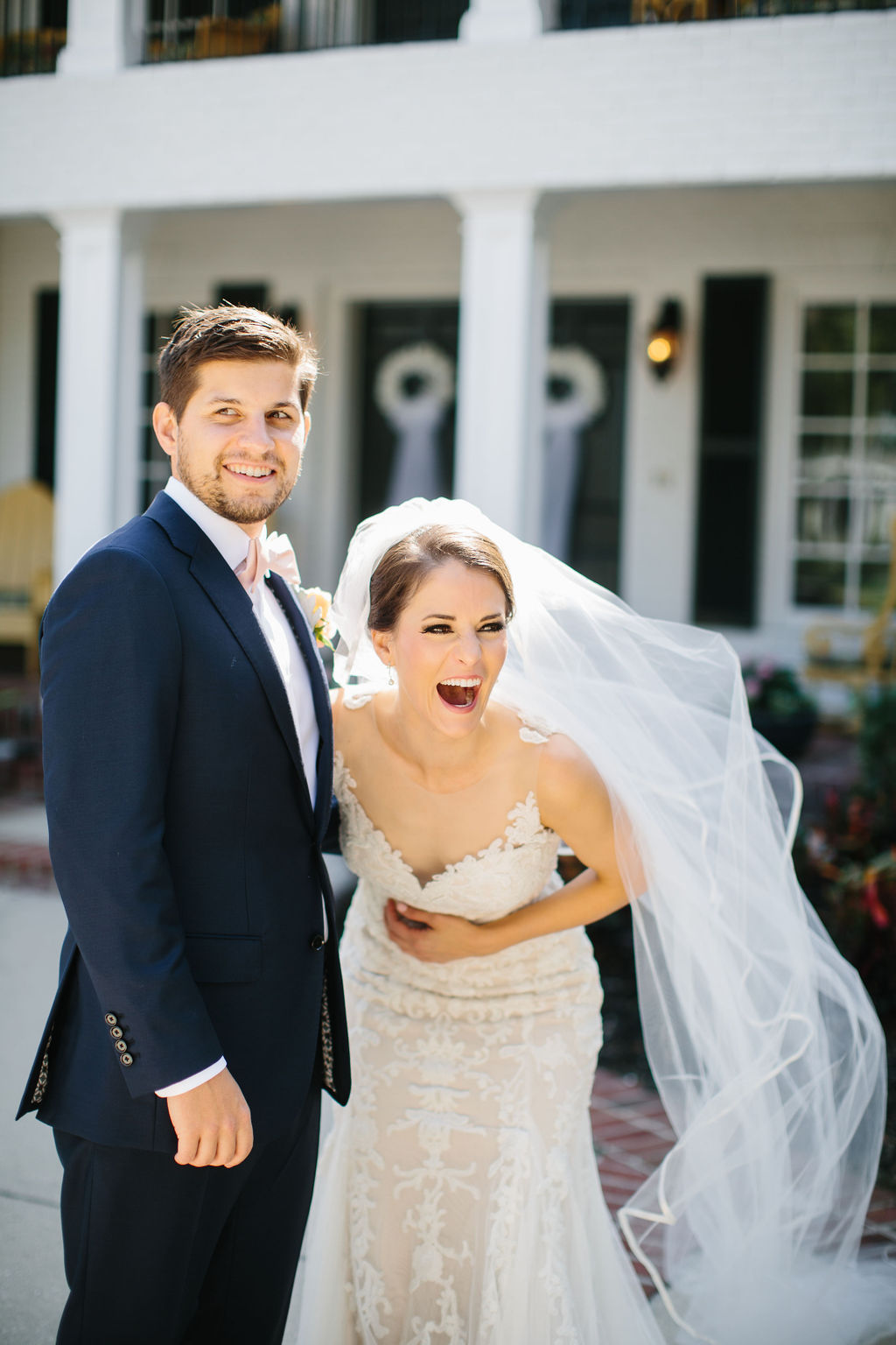 Fun Bride Laughing with Groom Portrait, Bride in Romantic Watters Lace and Illusion Neckline Wedding Dress with Full Length Veil, Groom in Blue Suit with Blush Pink Bowtie | Tampa Bay Wedding Hair and Makeup Femme Akoi Beauty Studio