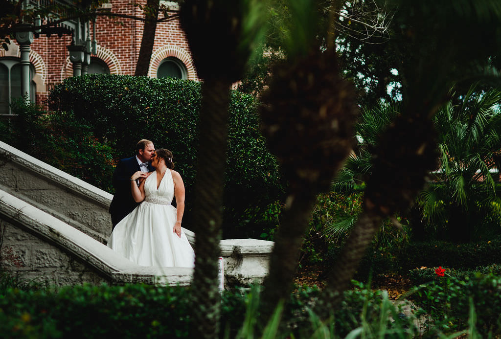 Florida Bride and Groom Wedding Portrait Outside University of Tampa, Wearing Romona Keveza Halter Styler Wedding Dress | Tampa Bay Wedding Planner Coastal Coordinating | South Tampa Dress Shop Isabel O'Neil Bridal Collection