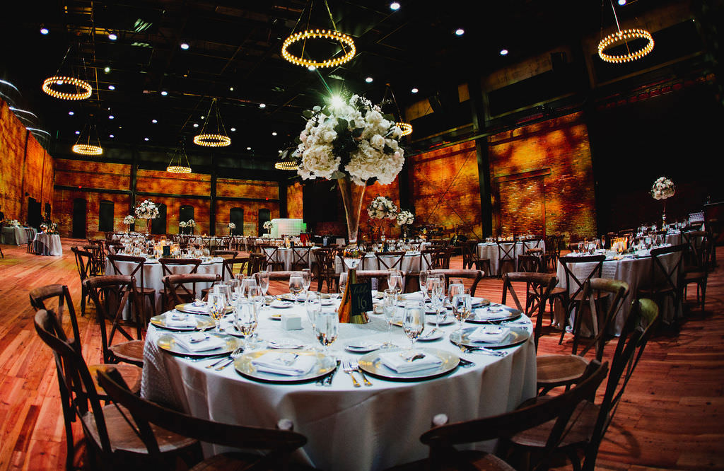 Classic Wedding Reception and Decor, Tall Elegant Centerpieces with Large White Floral Design, on Round Tables with White Lines, Farmhouse Cross Back Chairs, In The Gathering Ballroom At Armature Works in Tampa Heights | Downtown Tampa Wedding Planner Coastal Coordinating | Tampa Bay Entertainers Bay Kings Band