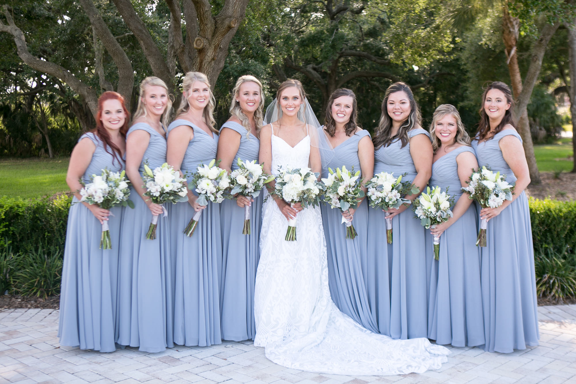 Bride in Romantic Lace Spaghetti Strap Sweetheart Neckline Wedding Dress Holding White and Eucalyptus Floral Bouquet, Bridesmaids in Matching Dusty Blue Dresses Wedding Portrait   Tampa Bay Wedding Photographer Carrie Wildes Photography   Wedding Planner Love Lee Lane