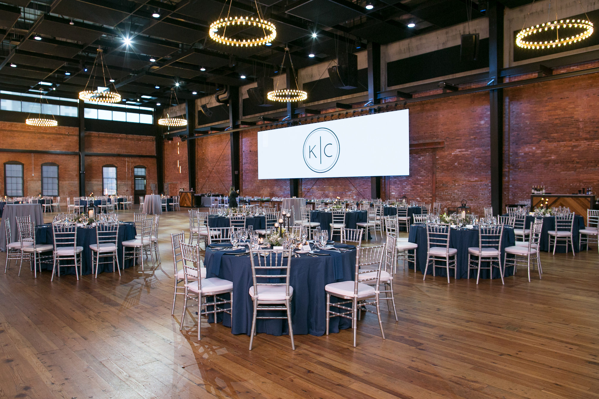 Modern Wedding Reception Decor, Round Tables with Navy Blue Linens, Silver Chiavari Chairs, Round Chandeliers, Custom Monogram Projection   Tampa Bay Wedding Photographer Carrie Wildes Photography   Wedding Planner Love Lee Lane   Historic Industrial Red Brick Wedding Reception Venue Armature Works   Chair and Table Rentals A Chair Affair