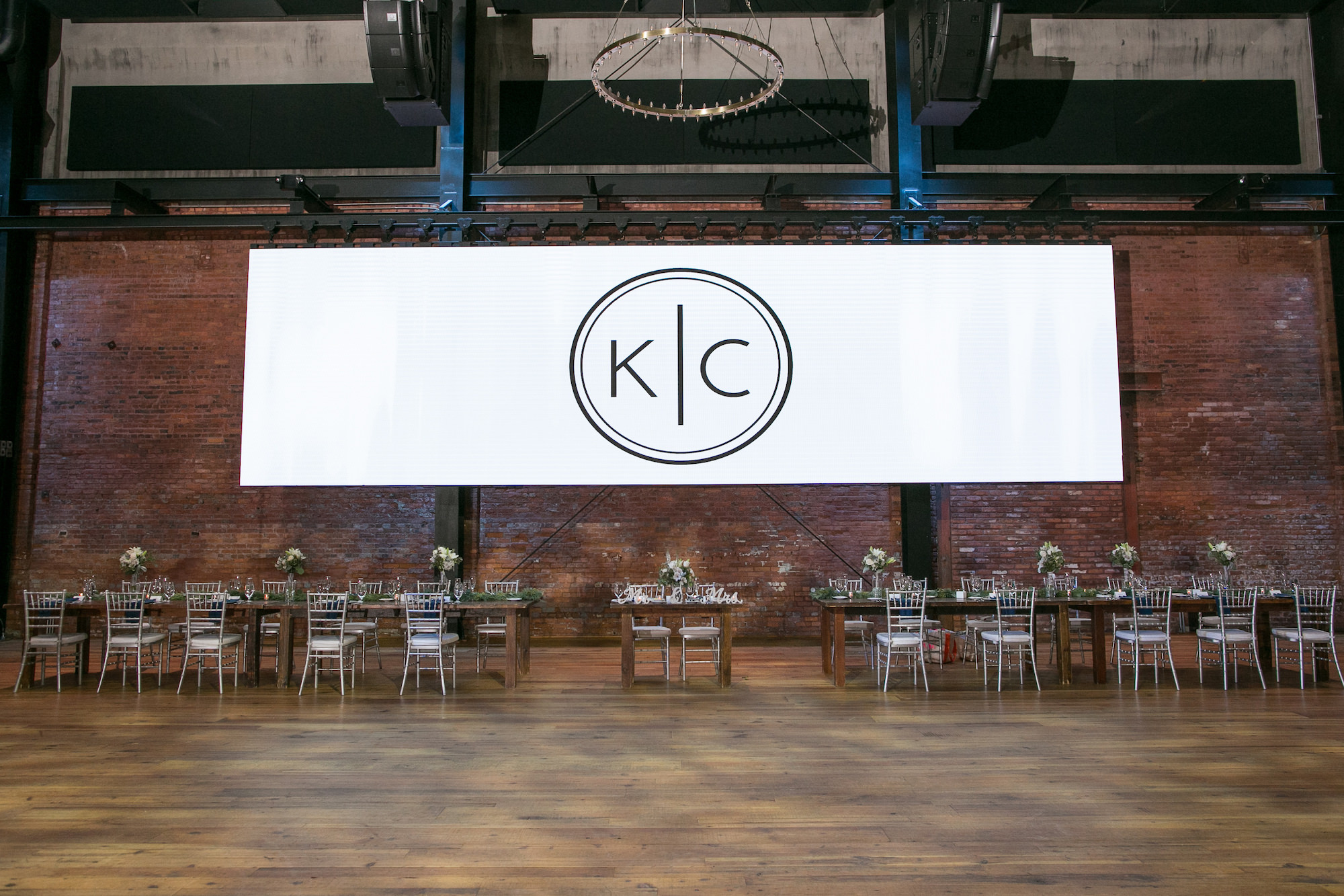 Large Custom Monogram White Banner, Long Wooden Feasting Tables with Silver Chiavari Chairs   Tampa Bay Wedding Photographer Carrie Wildes Photography   Wedding Planner Love Lee Lane   Industrial Historic Wedding Venue Armature Works   Chair and Table Rentals A Chair Affair