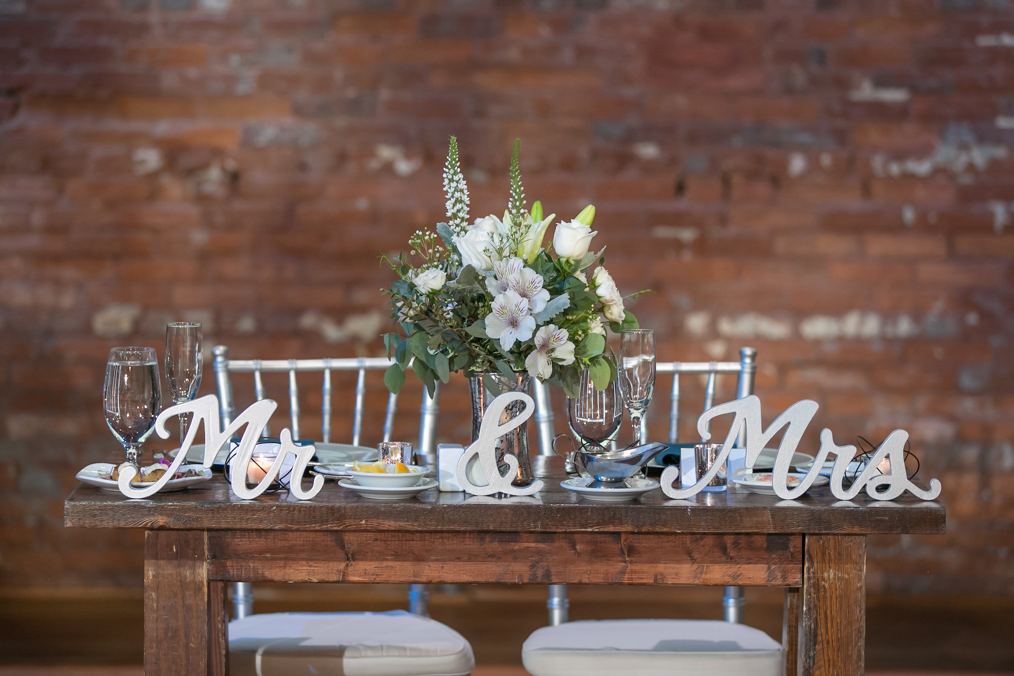 Rustic Wood Sweetheart Table with Silver Laser Cut Mr and Mrs Signage, Ivory Roses and Greenery Floral Bouquet, Silver Chiavari Chairs   Tampa Bay Wedding Photographer Carrie Wildes Photography   Chair and Table Rentals A Chair Affair   Wedding Planner Love Lee Lane