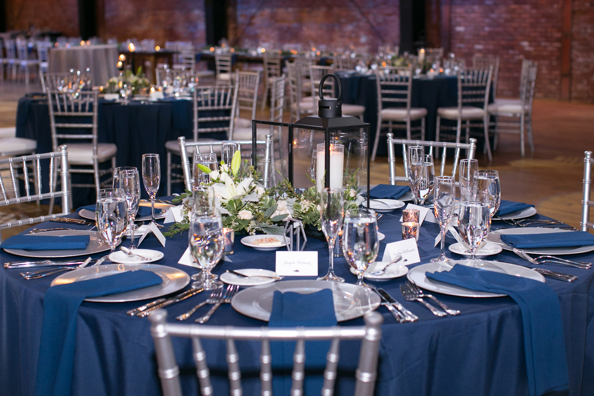 Modern Elegant Wedding Reception Decor, Round Table with Navy Blue Linens, Silver Chiavari Chairs and Chargers, Black Lantern with White Flowers and Greenery Centerpiece   Tampa Bay Wedding Photographer Carrie Wildes Photography   Chair, Chargers and Table Rentals A Chair Affair   Industrial Historic Wedding Venue Armature Works   Wedding Planner Love Lee Lane