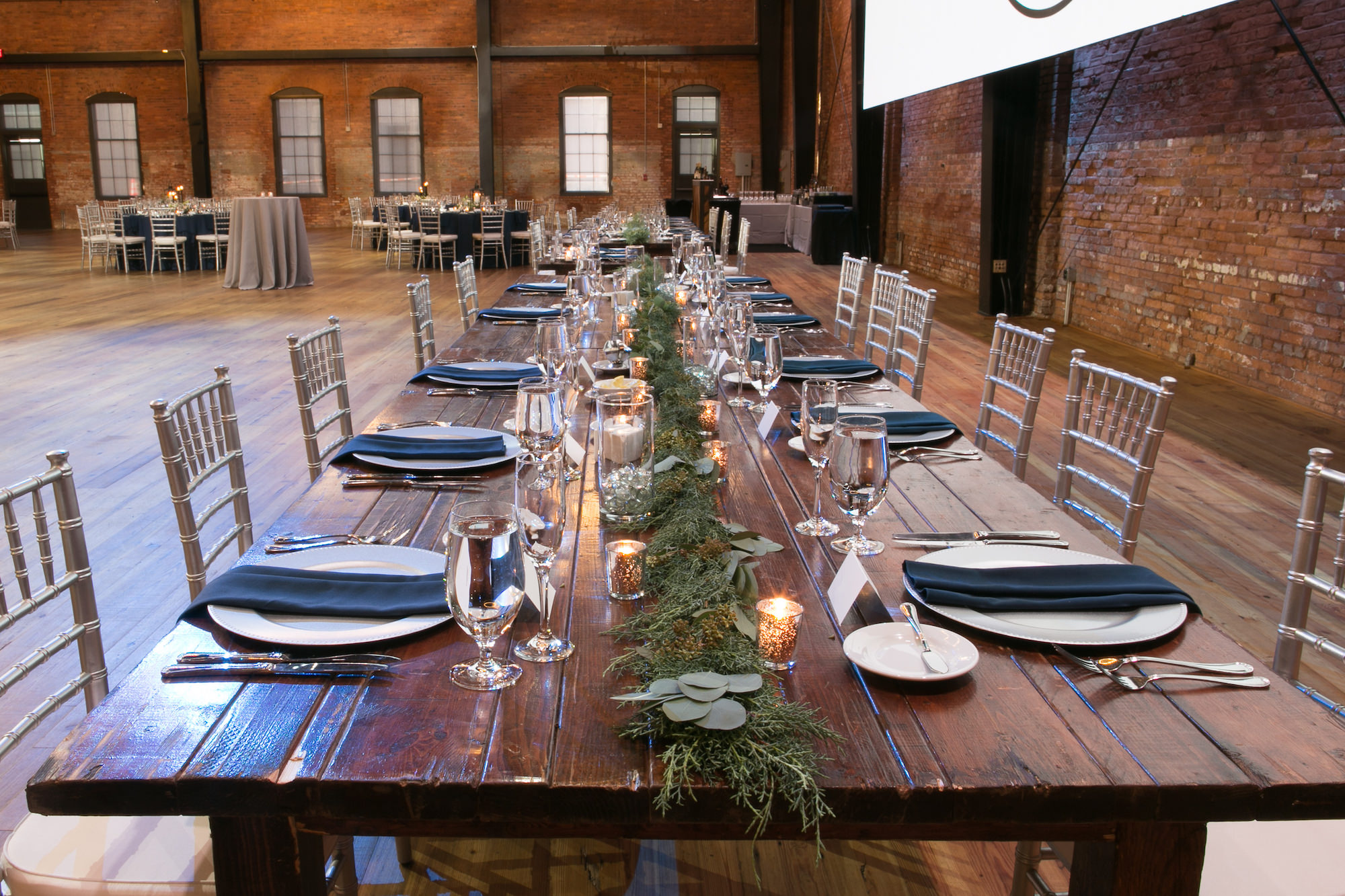 Rustic Wooden Long Feasting Table, Greenery Garland Table Runner, Silver Chiavari Chairs and Chargers   Tampa Bay Wedding Photographer Carrie Wildes Photography   Chair, Chargers and Table Rentals A Chair Affair   Historic Industrial Wedding Venue Armature Works   Wedding Planner Love Lee Lane