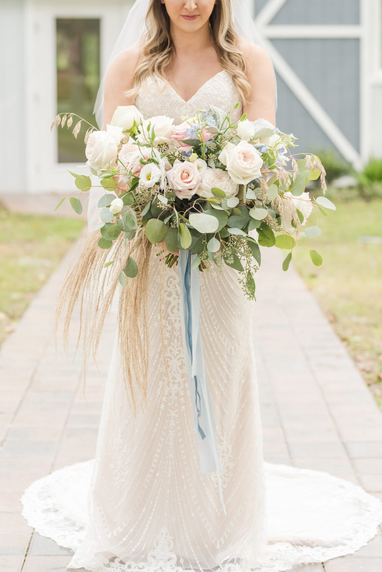 Florida Bride Holding Vintage Meets Rustic Bridal Bouquet with Light Pink Roses, Ivory Flowers, Dusty Rose Florals, Eucalyptus Leaves and Greenery, Pompous Grass, Dusty Blue Ribbon, Wearing Romantic Beaded Wedding Dress | Tampa Bay Wedding Planner Elegant Affairs by Design