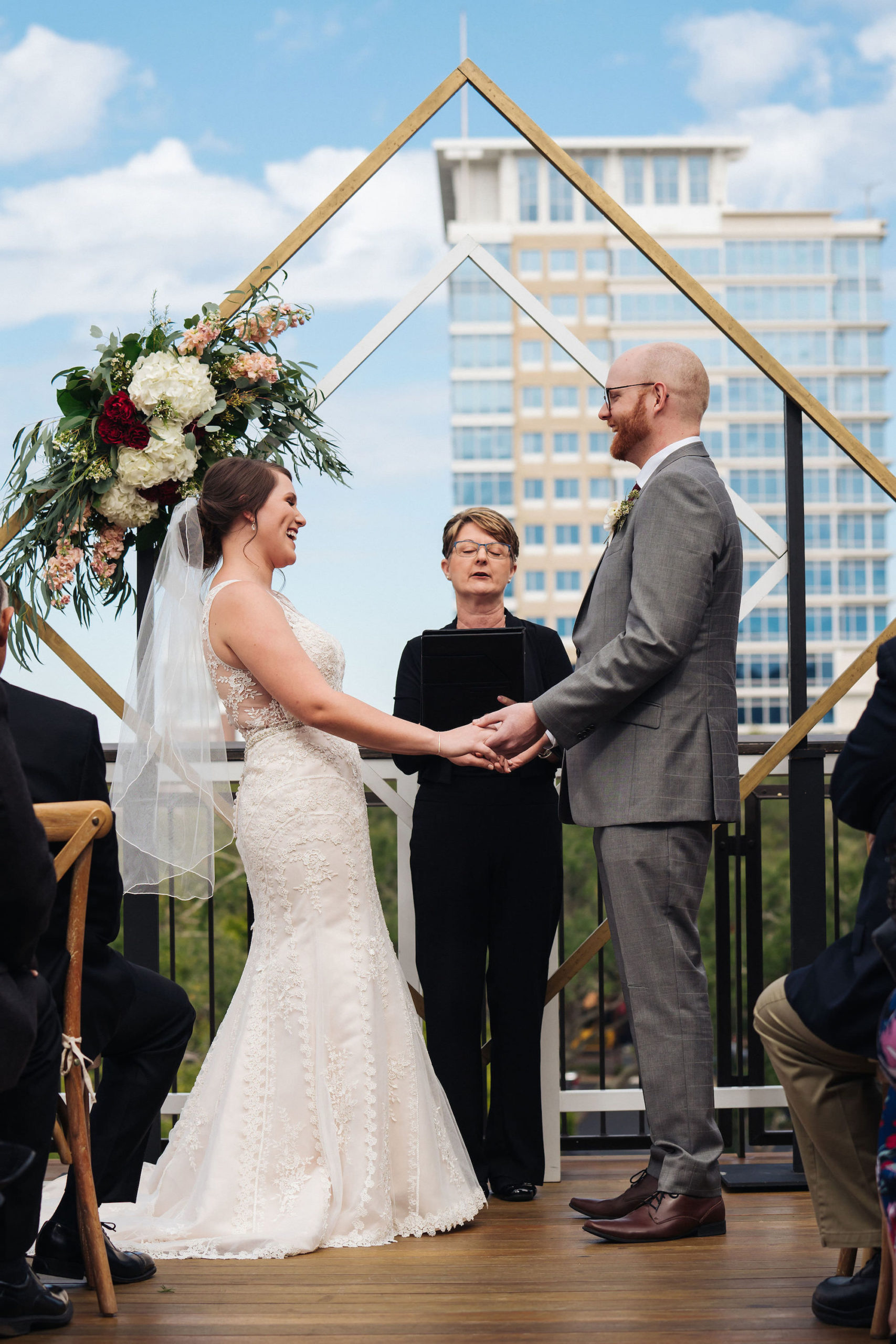 St. Petersburg Florida Wedding Venue   St. Pete Red Mesa Events   Rooftop Geometric Gold Ceremony Arch Backdrop   Lace Bridal Gown   Groom Grey Suit