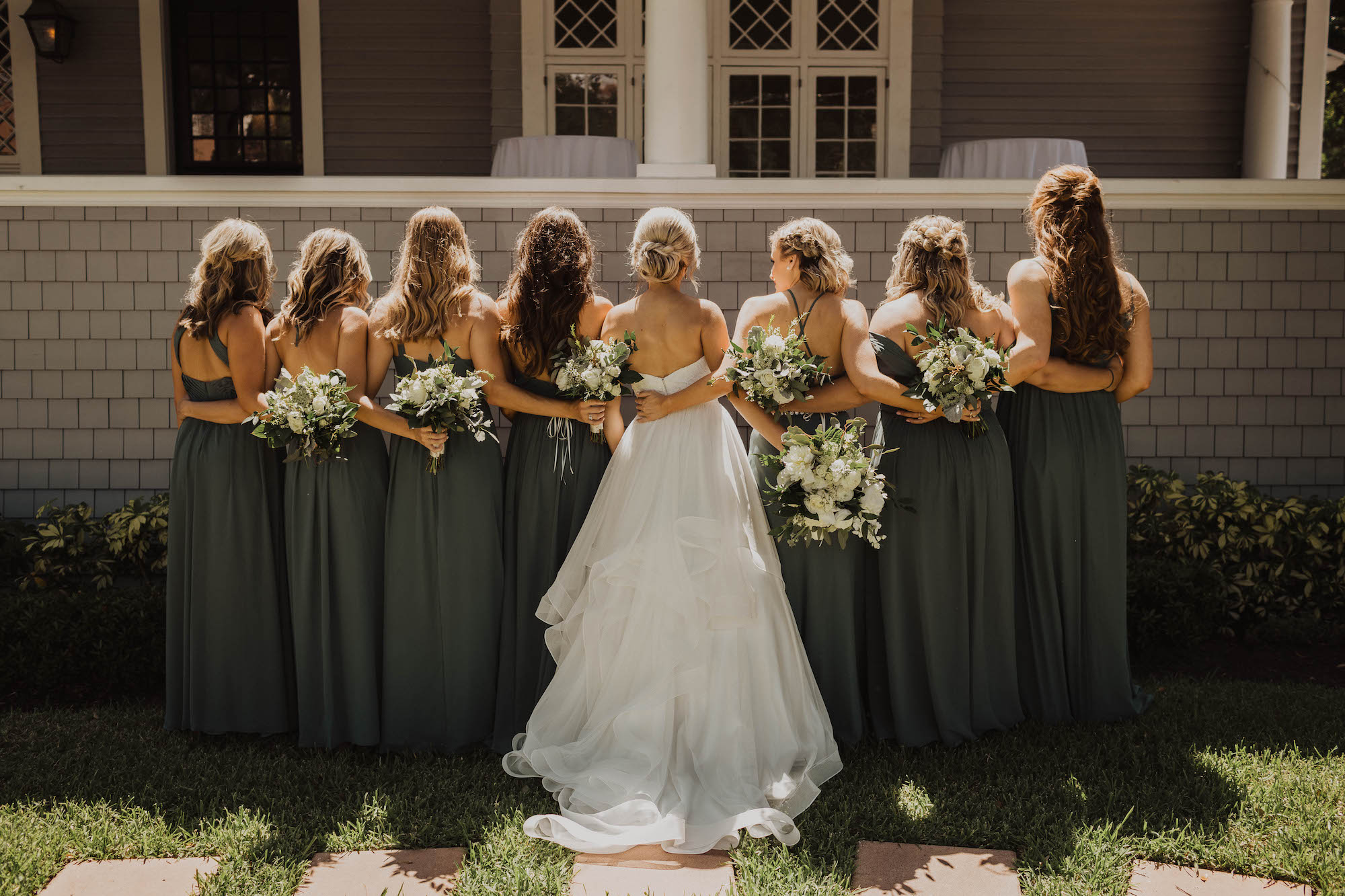 Tampa Bay Bride and Bridesmaids in Mix and Match Eucalyptus Green Dresses Holding Garden Inspired White Roses and Greenery Floral Bouquets