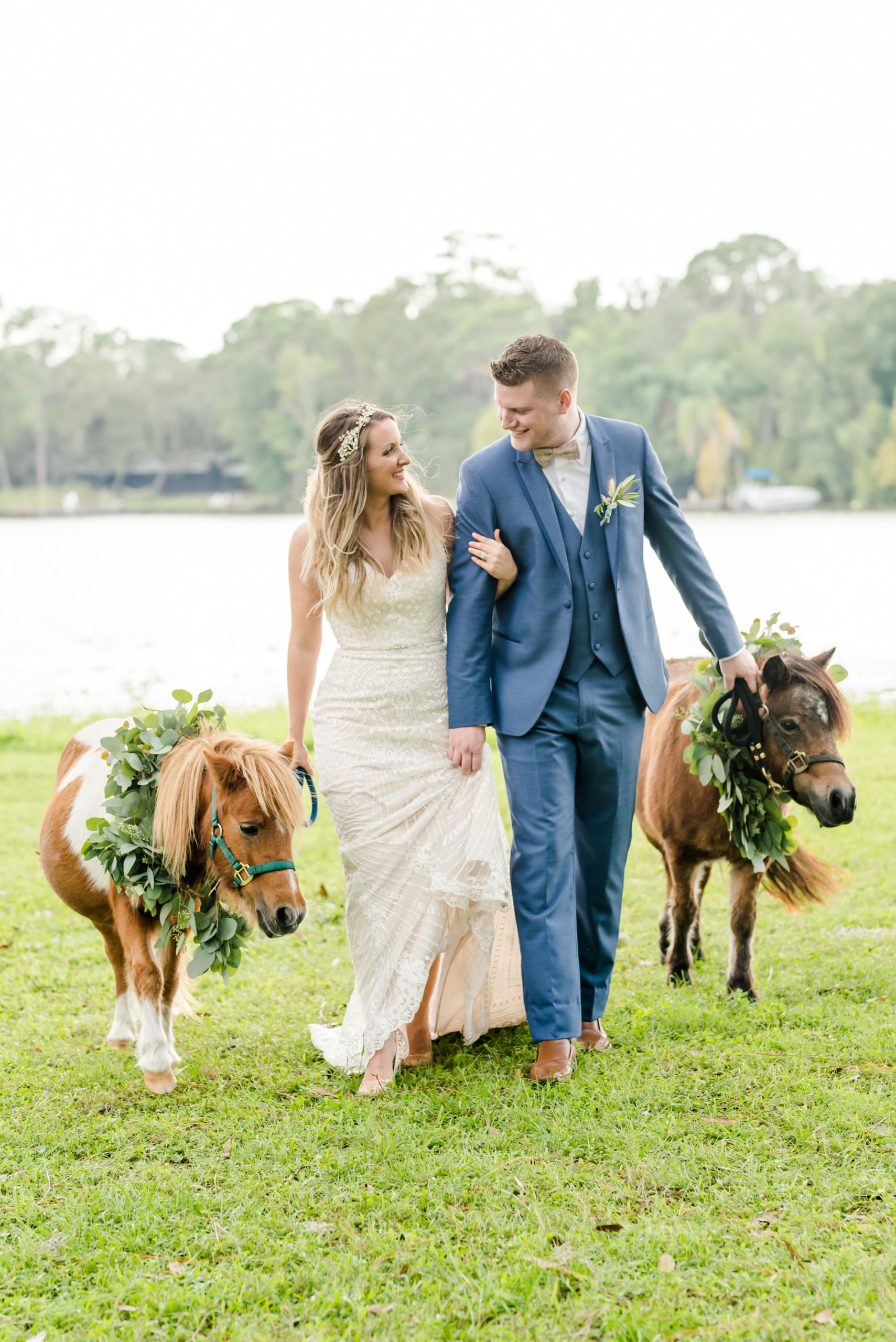 Florida Bride and Groom Wedding Portrait with Minature Ponies, Bride Wearing Strapless Beaded Sheath Wedding Dress, Groom in Muted Navy Suit, with Greenery Eucalyptus Leaves for Formal Pet Collar