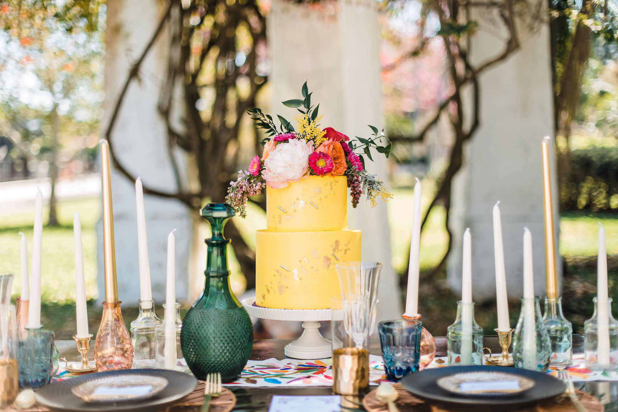 Outdoor Whimsical Wedding Reception Styled Shoot with Yellow Two Tiered Cake with Metallic Accent and Tropical Florals
