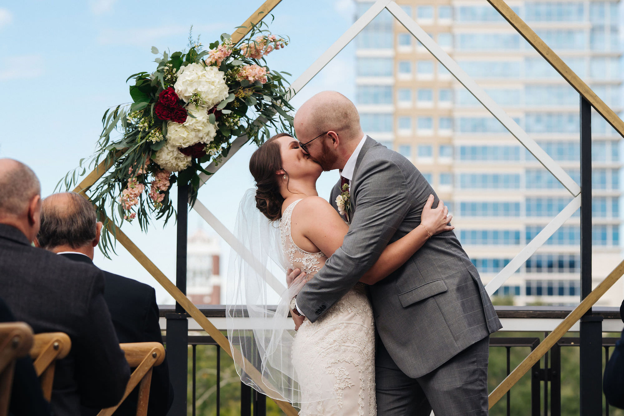 St. Petersburg Florida Wedding Venue   St. Pete Red Mesa Events   Rooftop Geometric Gold Ceremony Arch Backdrop   Lace Bridal Gown   Groom Grey Suit   First Kiss