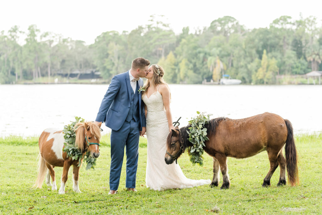 Florida Bride and Groom Wedding Portrait with Miniature Ponies, Bride Wearing Strapless Beaded Sheath Wedding Dress, Groom in Muted Navy Suit, with Greenery Eucalyptus Leaves for Formal Pet Collar | Tampa Bay Wedding Planner Elegant Affairs by Design