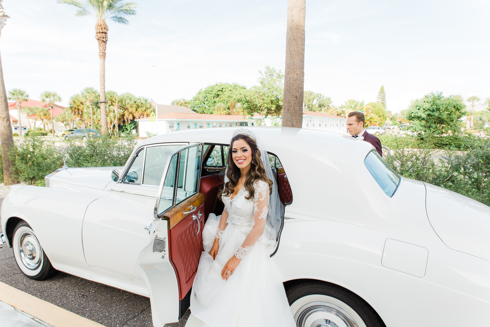 Elegant Bride Wearing Hayley Paige Wedding Dress with Lace Long Sleeve Cover with Vintage White Car