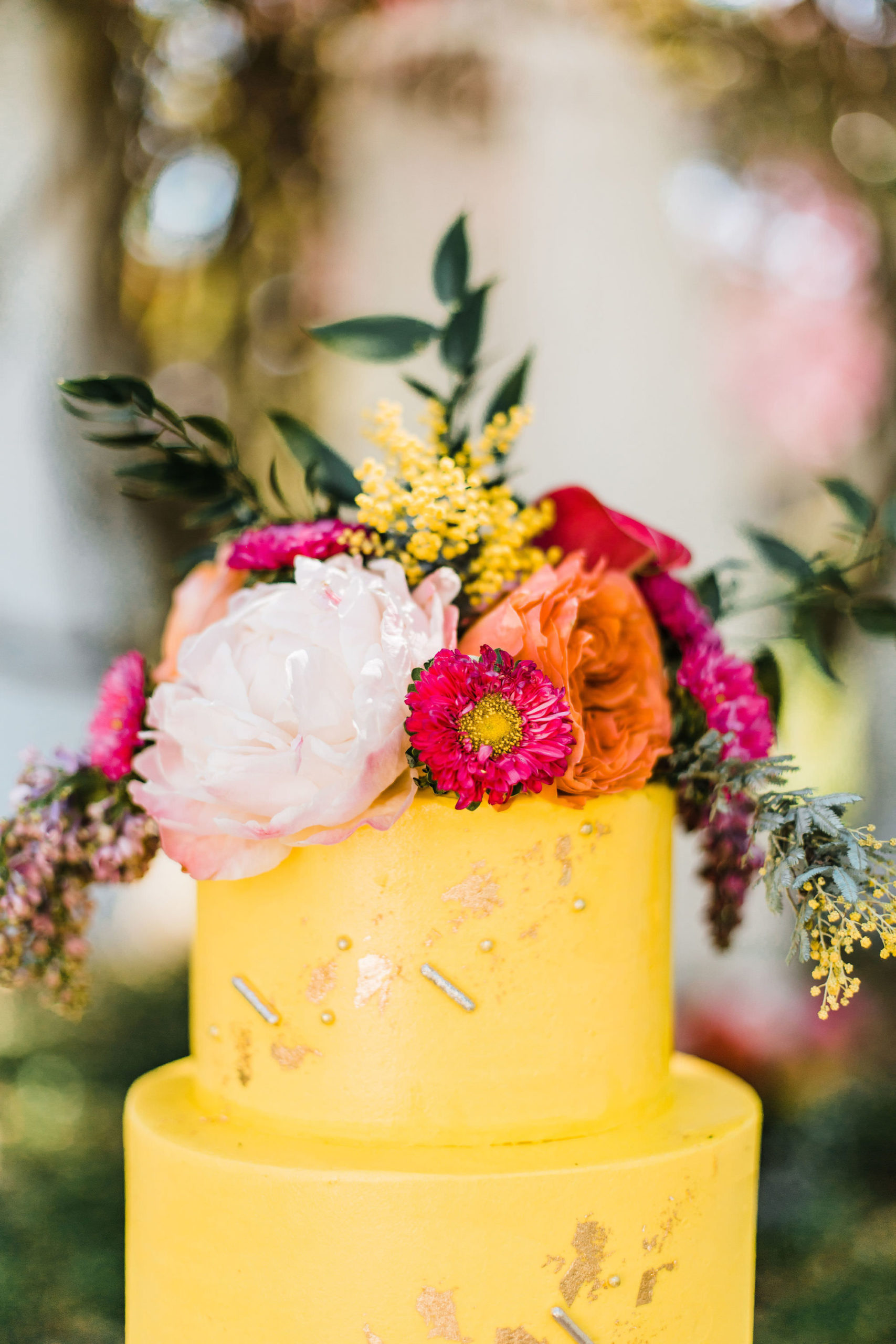 Yellow with Gold Metallic Accent Two Tiered Cake with Tropical Inspired Flowers | Wandering Whisk Bakeshop