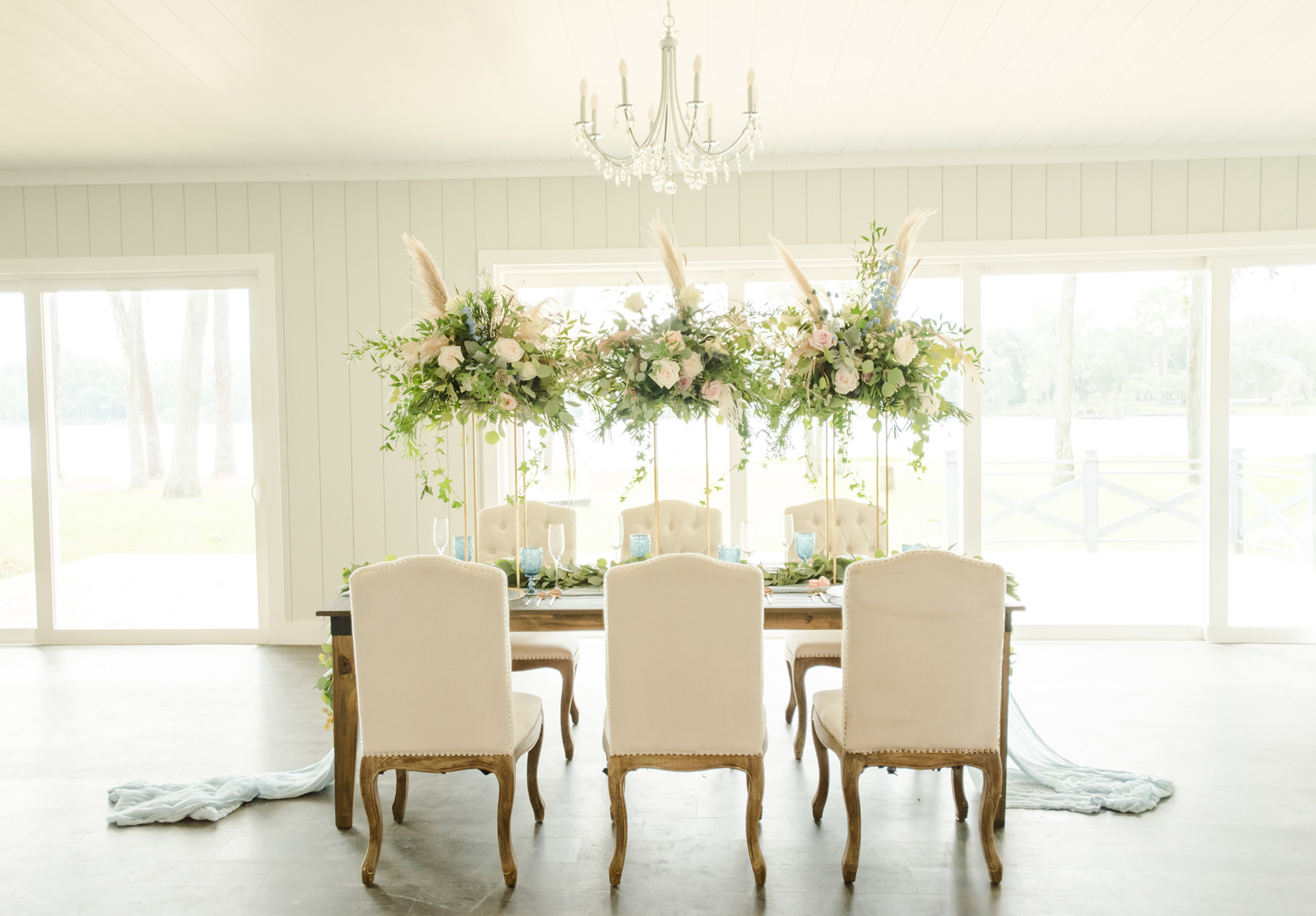 Dusty Rose Styled Wedding Shoot, Antique Off White Ivory Chairs, Wood Table with Tall Gold Frame Stands, Greenery, Blush Pink and White Roses, and Feather Floral Arrangements, Blue Wine Glasses   Tampa Bay Wedding Planner Elegant Affairs by Design   Odessa Rustic Waterfront Wedding Venue Barn at Crescent Lake
