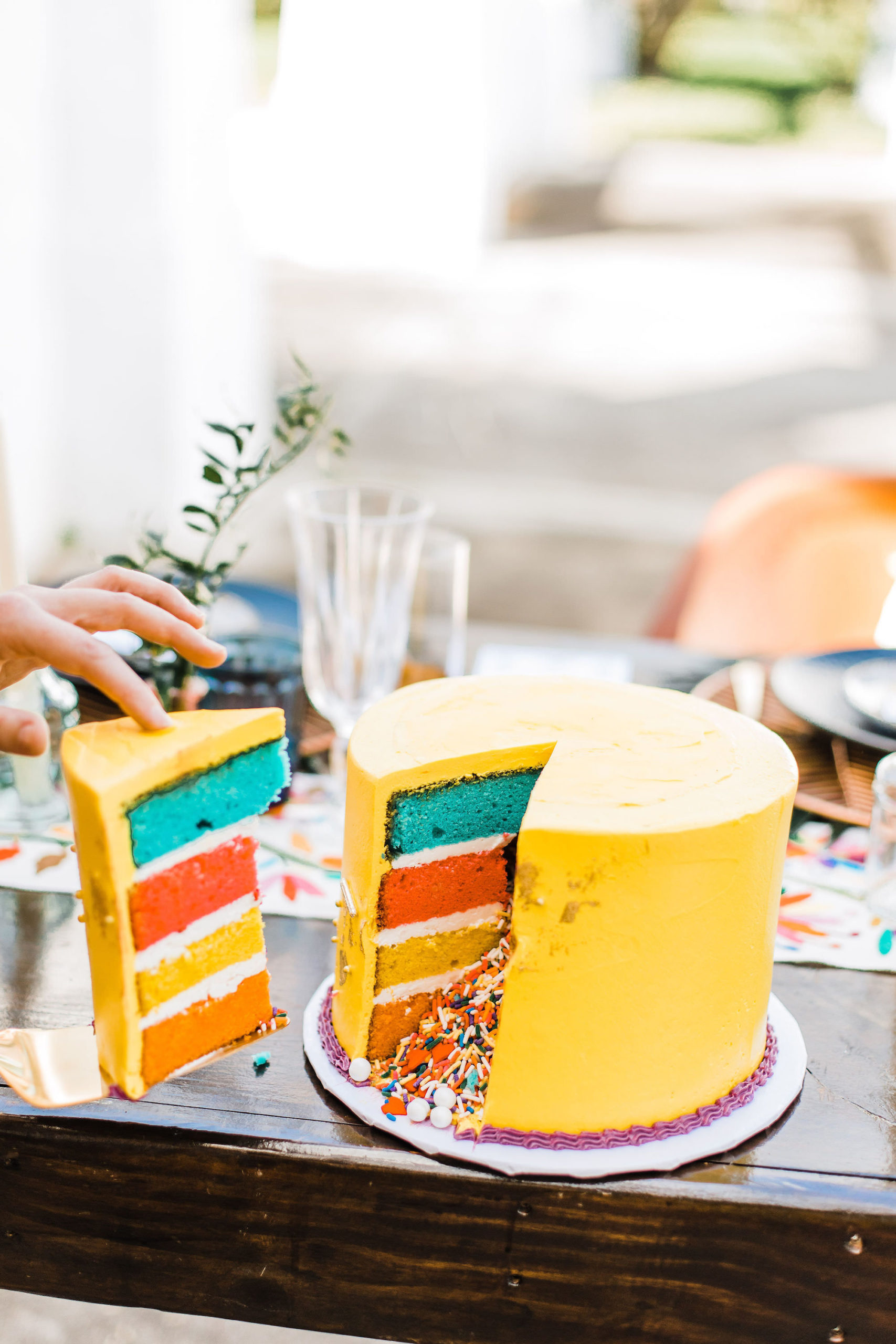 Yellow Four Tiered Colorful Confetti Sprinkle Explosion Cake with Rainbow Accents | Wandering Whisk Bakeshop