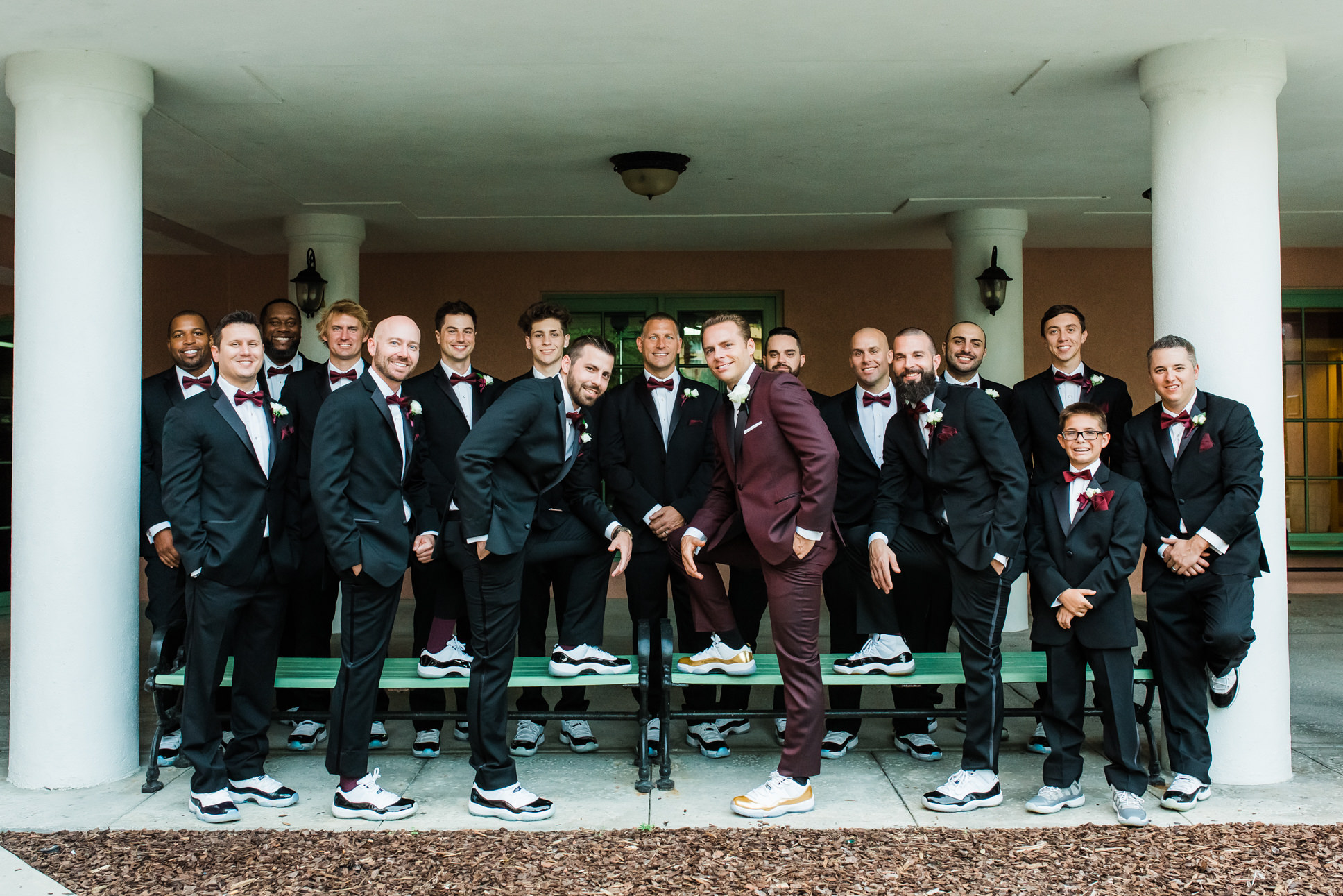Groom in Burgundy Suit with White and Gold Sneakers, Groomsmen in Black Suits with Matching White and Black Sneakers and Burgundy Bowties Wedding Party Portrait
