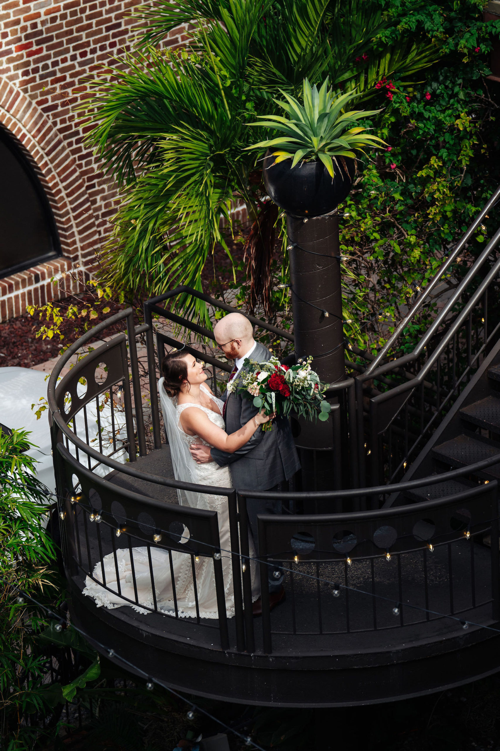 St. Petersburg Florida Wedding Venue   Red Mesa Events   Lace V Neck Bridal Gown   Groom Grey Suit Red Neck Tie
