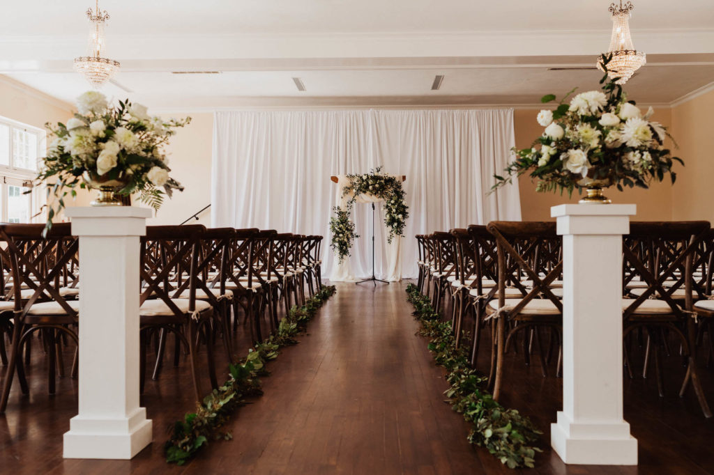 Simple Elegant Wedding Ceremony Decor, Mahogany Chiavari Chairs, White Pedestals with Ivory Roses and Eucalyptus Arrangements, White Draping and Arch | South Tampa Wedding Venue The Orlo