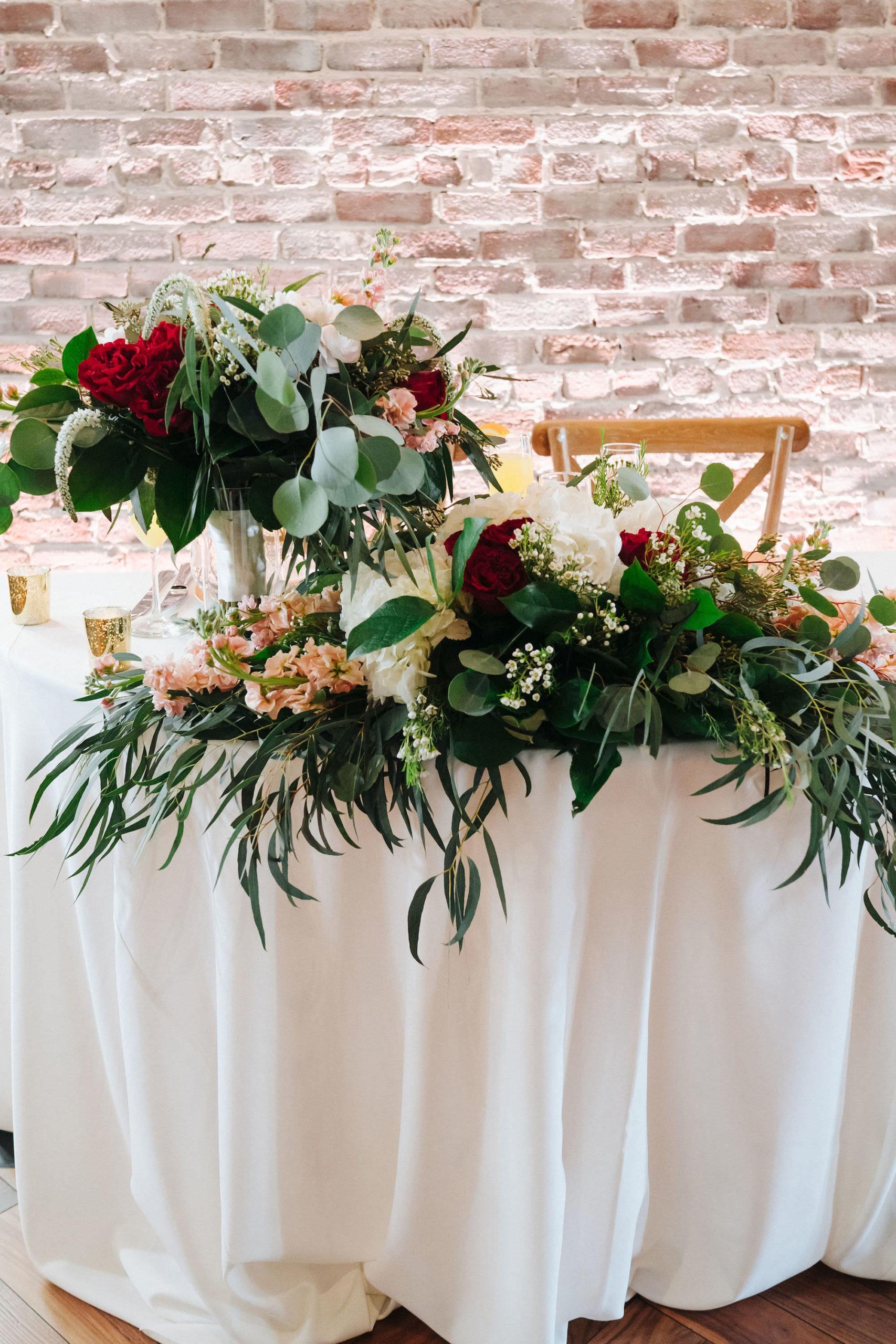 St. Pete Wedding   Bride and Groom Sweetheart Table   Blush Red Garnet Greenery Natural Boho Floral Arrangement