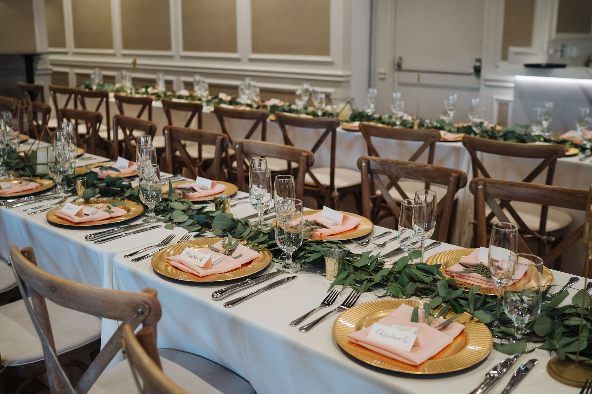 St. Petersburg Florida Wedding Venue   Red Mesa Events   Reception Long Banquet Feasting Tables   Wood Cross Back French Country Chairs   Greenery Garland Centerpiece with Gold Chargers and Blush Napkins