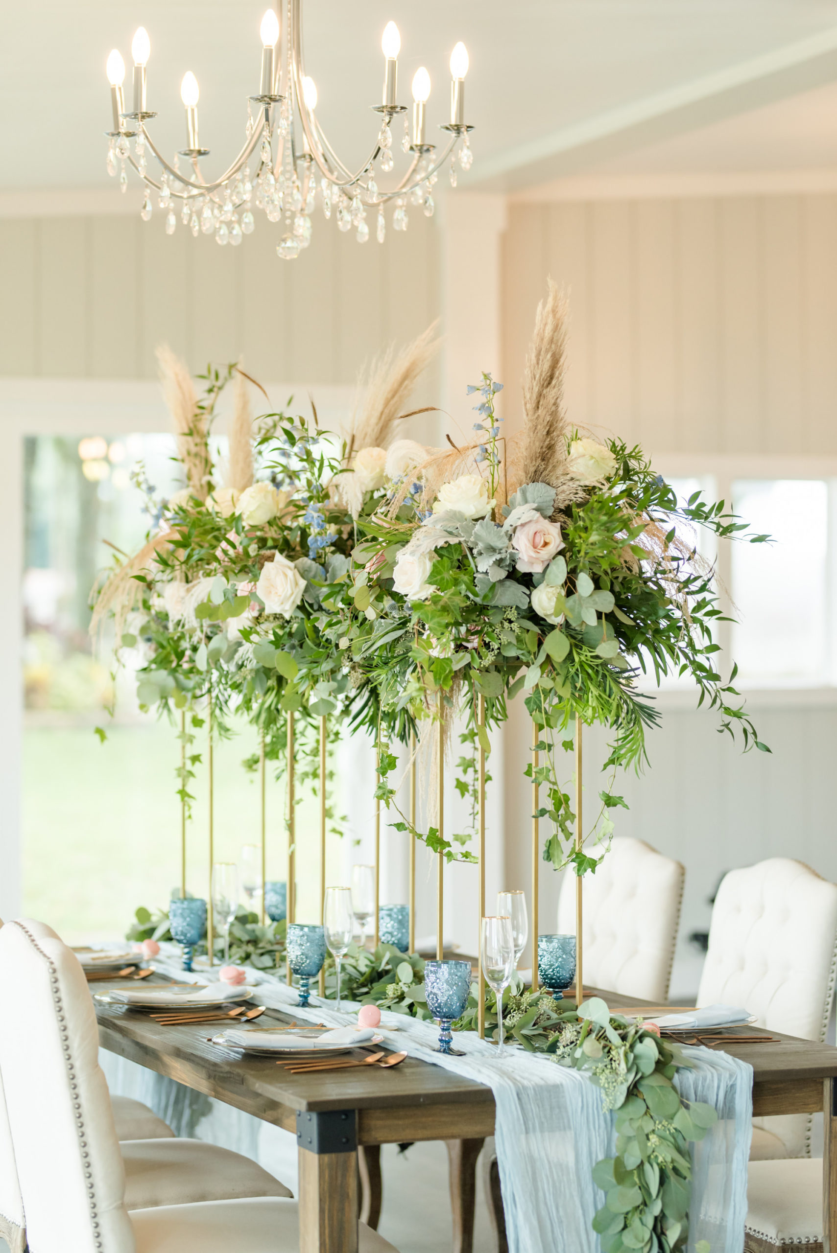 Dusty Rose Styled Wedding Shoot, Antique Off White Ivory Cushion Chairs, Wood Table with Tall Gold Frame Stands, Greenery, Blush Pink and White Roses, and Feather Floral Arrangements, Blue Wine Glasses, White Fabric and Eucalyptus Garland Table Runner   Tampa Bay Wedding Planner Elegant Affairs by Design   Odessa Rustic Waterfront Wedding Venue Barn at Crescent Lake