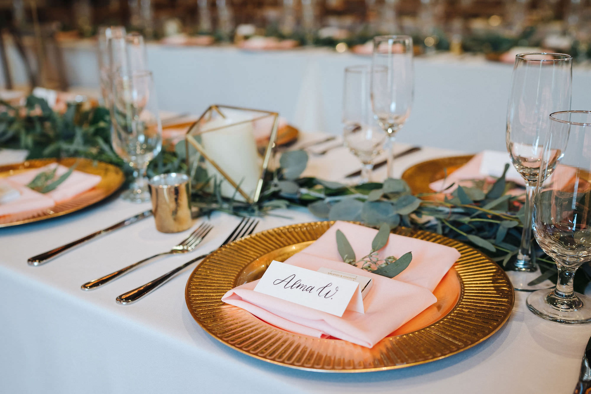 St. Petersburg Florida Wedding Venue   Red Mesa Events   Reception Long Banquet Feasting Tables   Wood Cross Back French Country Chairs   Greenery Garland Centerpiece with Gold Chargers and Blush Napkins   Gold Geometric Candles   Calligraphy Place Cards