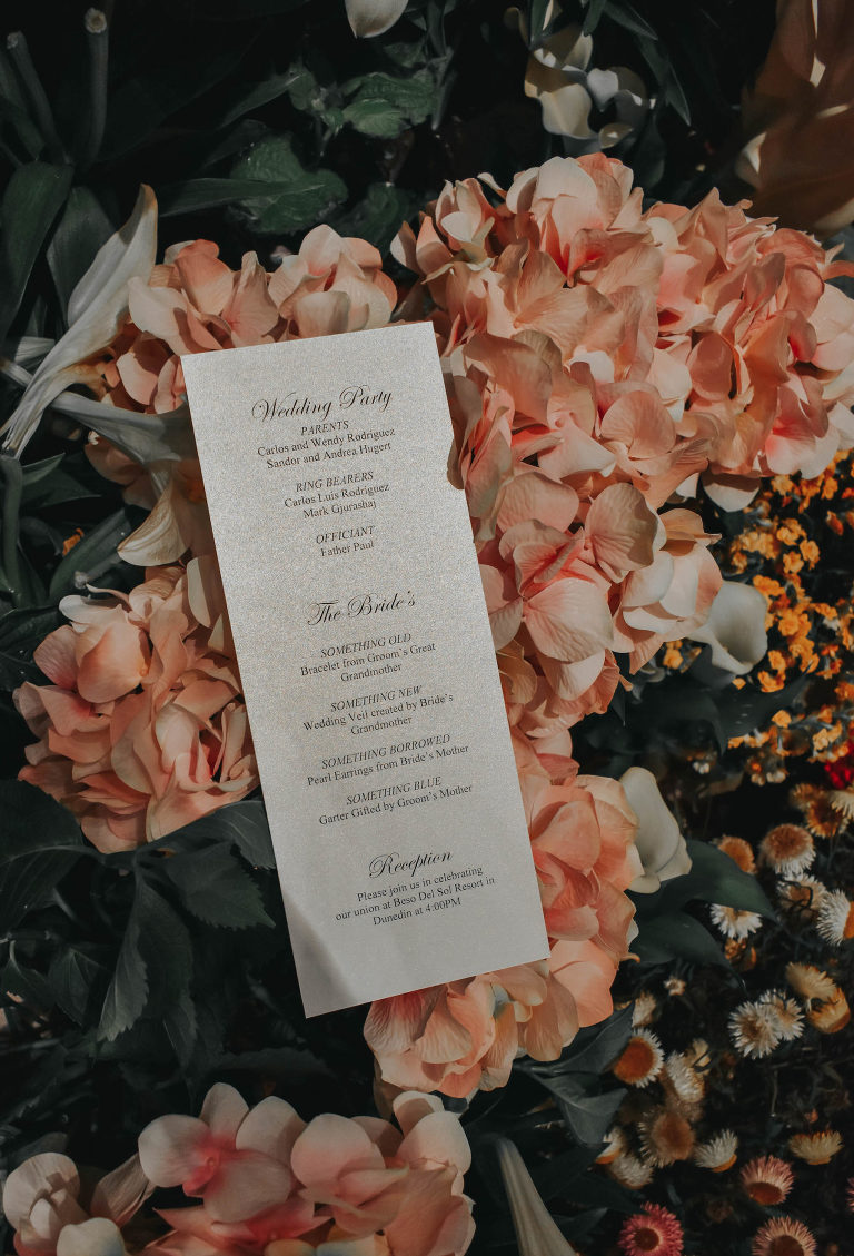 Classic Black and White Script Florida Wedding Ceremony Program, Sitting on Pink Floral Backdrop