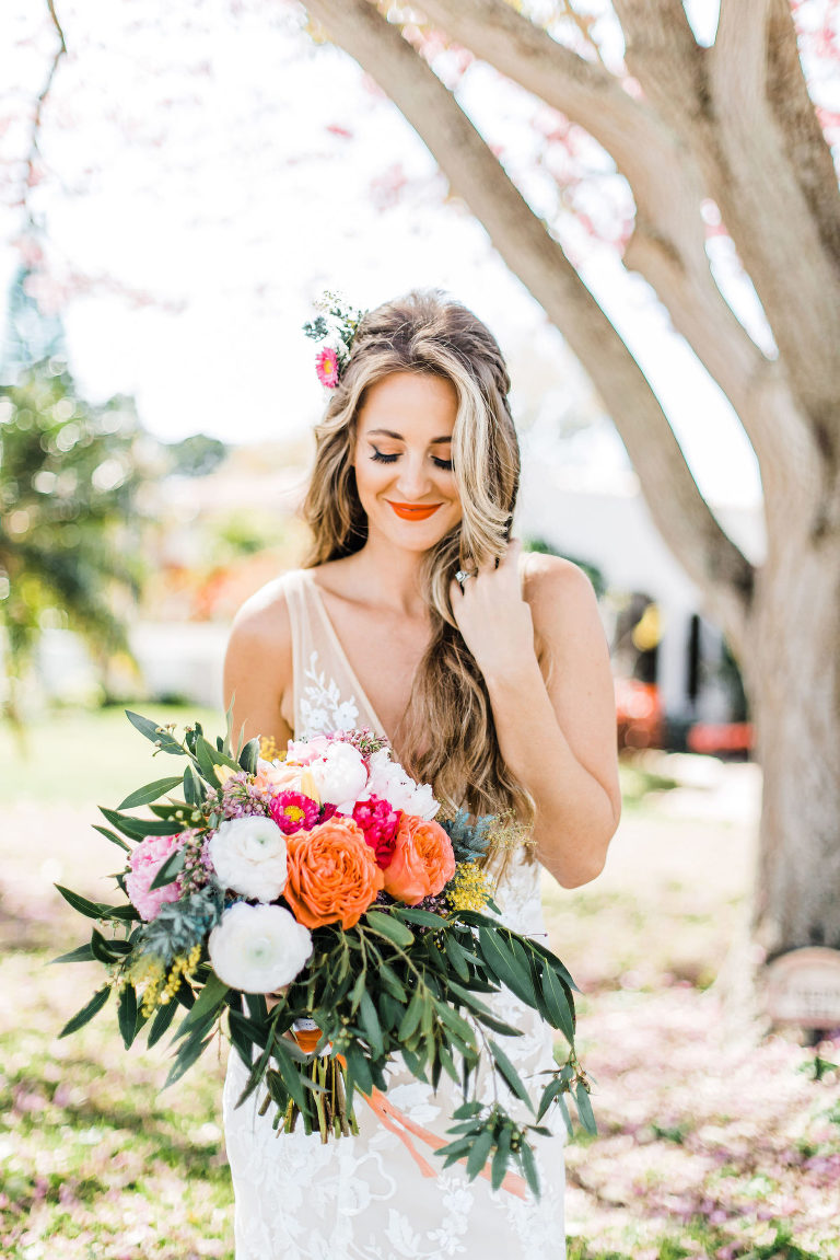 Boho Inspired Outdoor Bridal Portrait with Whimsical Colorful Bouquet and Bright Lip Color with Natural Waves and Flowers in Hair