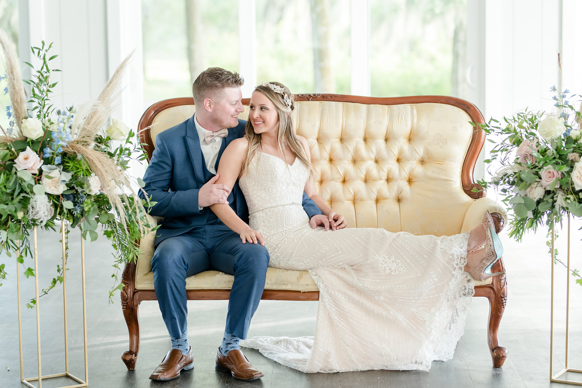Dusty Rose Styled Wedding Shoot, Romantic Bride Wearing Strapless Beaded Sheath Wedding Dress, Rhinestone Leaf Headband, Pointed Toe Clear and Rhinestone Wedding Shoes, Lounging on Antique Ivory and Wood Loveseat with Groom in Blue Tuxedo Tall Gold Geometric Frame Stands with Blush Pink and Ivory Roses, Greenery, Eucalyptus, Blue Flowers and Feather Floral Arrangements   Tampa Bay Wedding Planner Elegant Affairs by Design