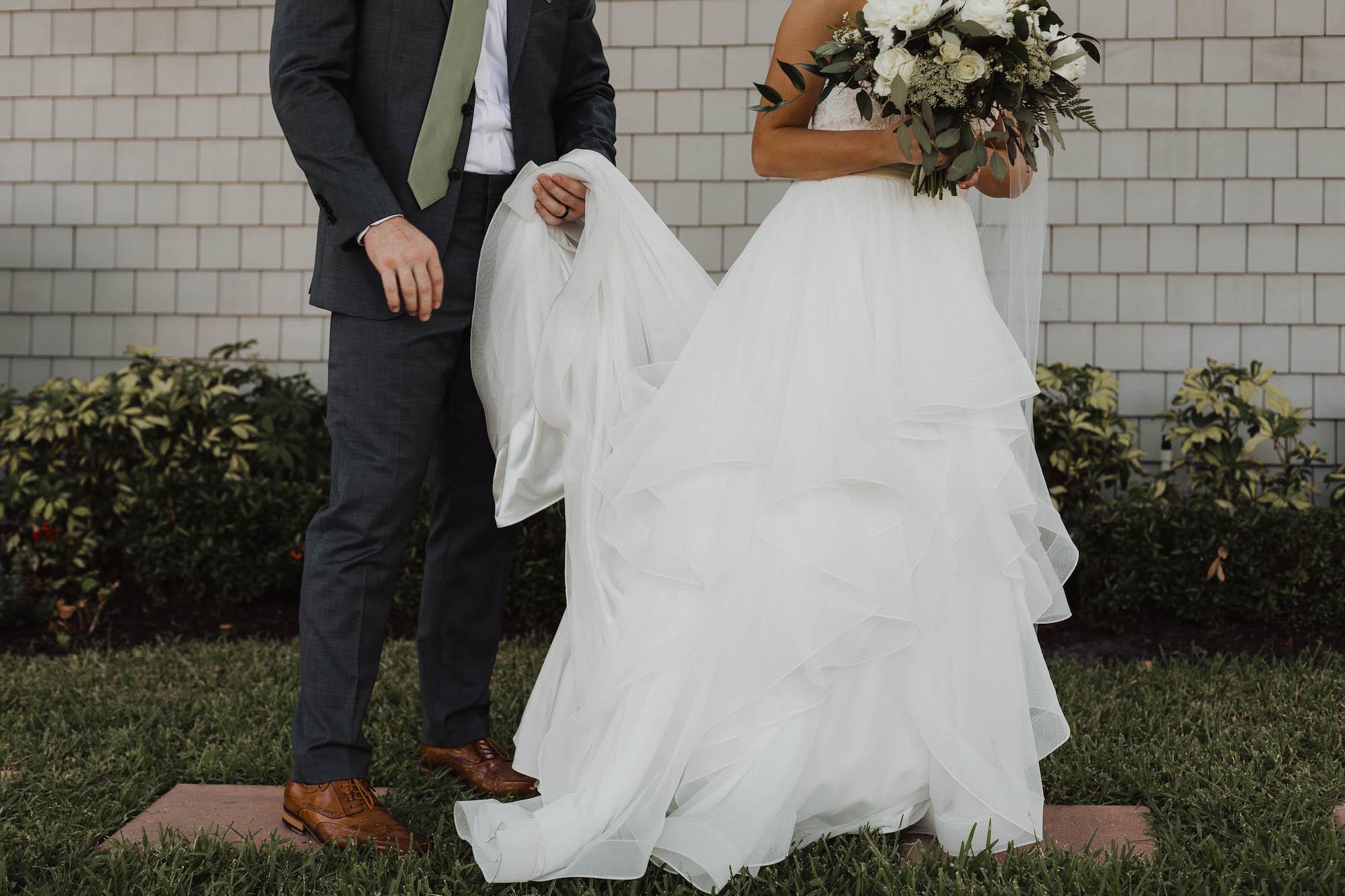 Creative Tampa Groom Holding Bride's Mikaella Cascading Ruffled Skirt Wedding Dress Skirt Portrait