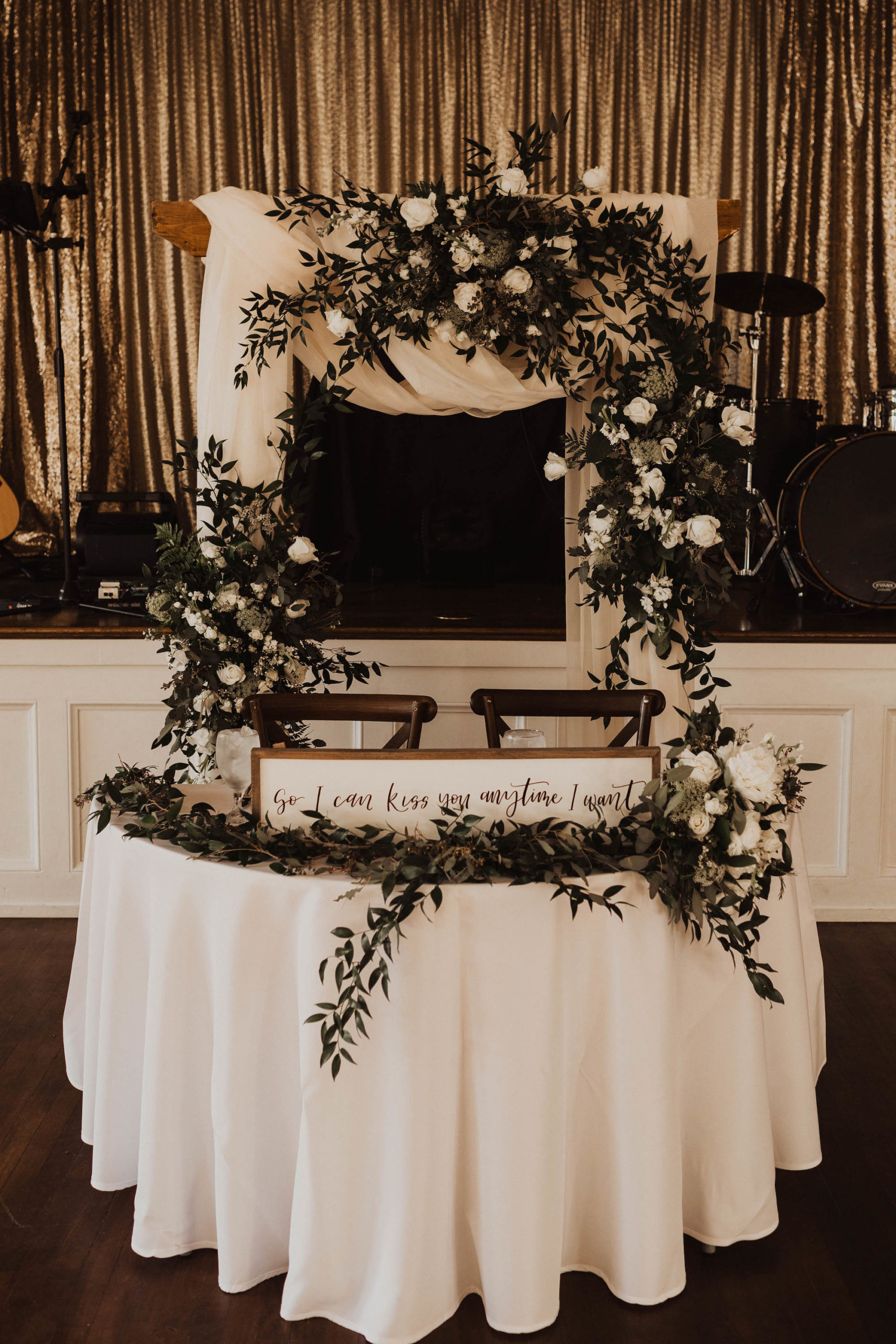 Simple Elegant Wedding Reception Decor Sweetheart Table With White Tablecloth Eucalyptus Greenery Garland Wooden Signage Wood Chiavari Chairs Arch With White Draping And Eucalyptus Greenery And Ivory Roses Arrangements Marry Me