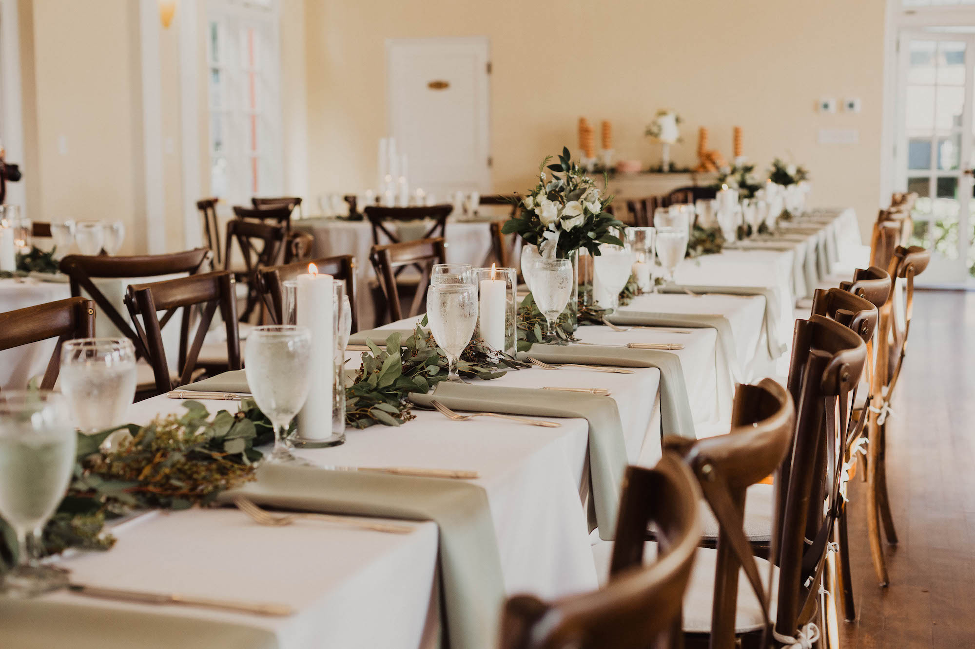Simple Elegant Wedding Reception Decor Long Feasting Table With White Tablecloths Sage Green Linen Napkins Wood Chiavari Chairs Eucalyptus Greenery Garland South Tampa Wedding Venue The Orlo Marry Me Tampa