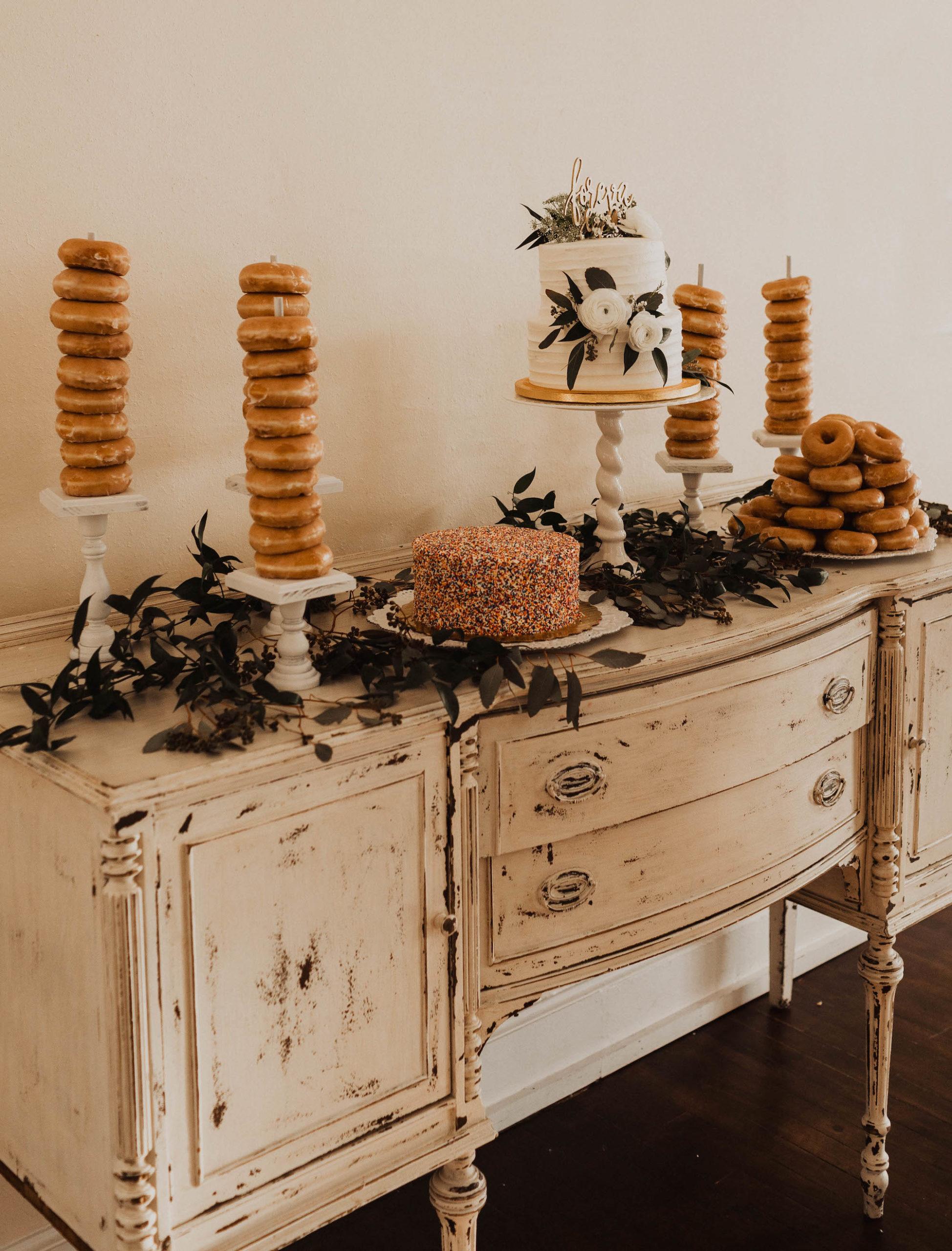 Antique White Dresser Dessert Table Setup, Krispy Kreme Donuts on Spindles, Two Tier White Ruffled Wedding Cake with Roses and Eucalyptus