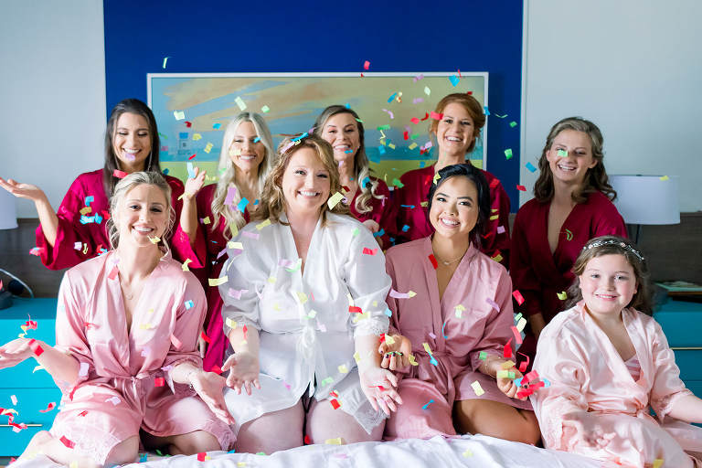 Bride and Bridesmaids Fun Colorful Confetti Throwing Wedding Portrait in Pink and Red Robes | Tampa Bay Wedding Photographer Shauna and Jordon Photography