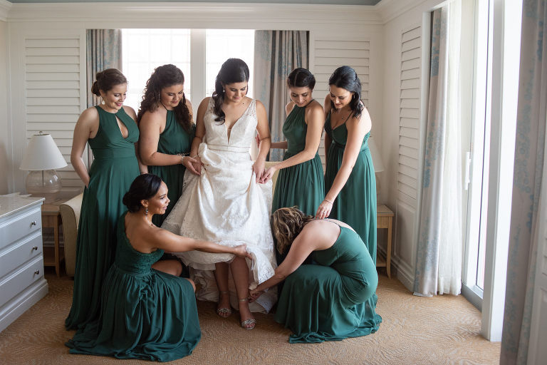 Tampa Bay Bride in Deep V Neckline Double Beaded Bands Across Waist, Paloma Blanca Lace Wedding Dress, Bridesmaids in Dark Green Mix and Match Azazie Dresses Getting Ready Wedding Portrait