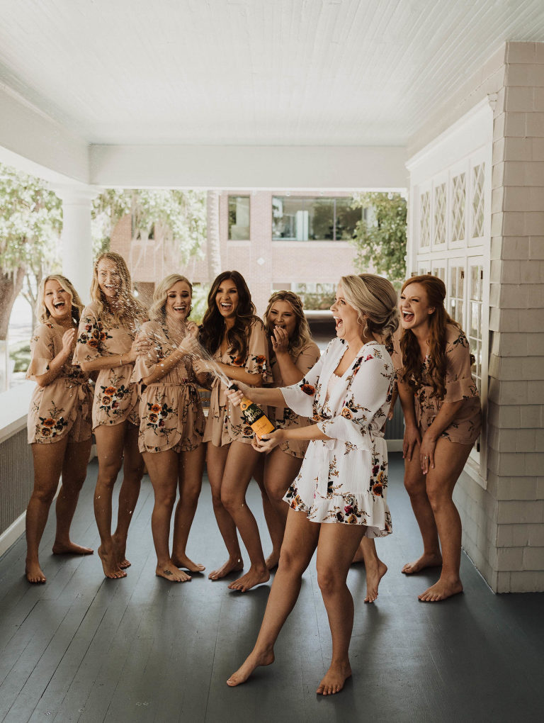 Tampa Bay Fun Bride and Bridesmaids in Floral Peach Rompers Popping Champagne Bottle Portrait
