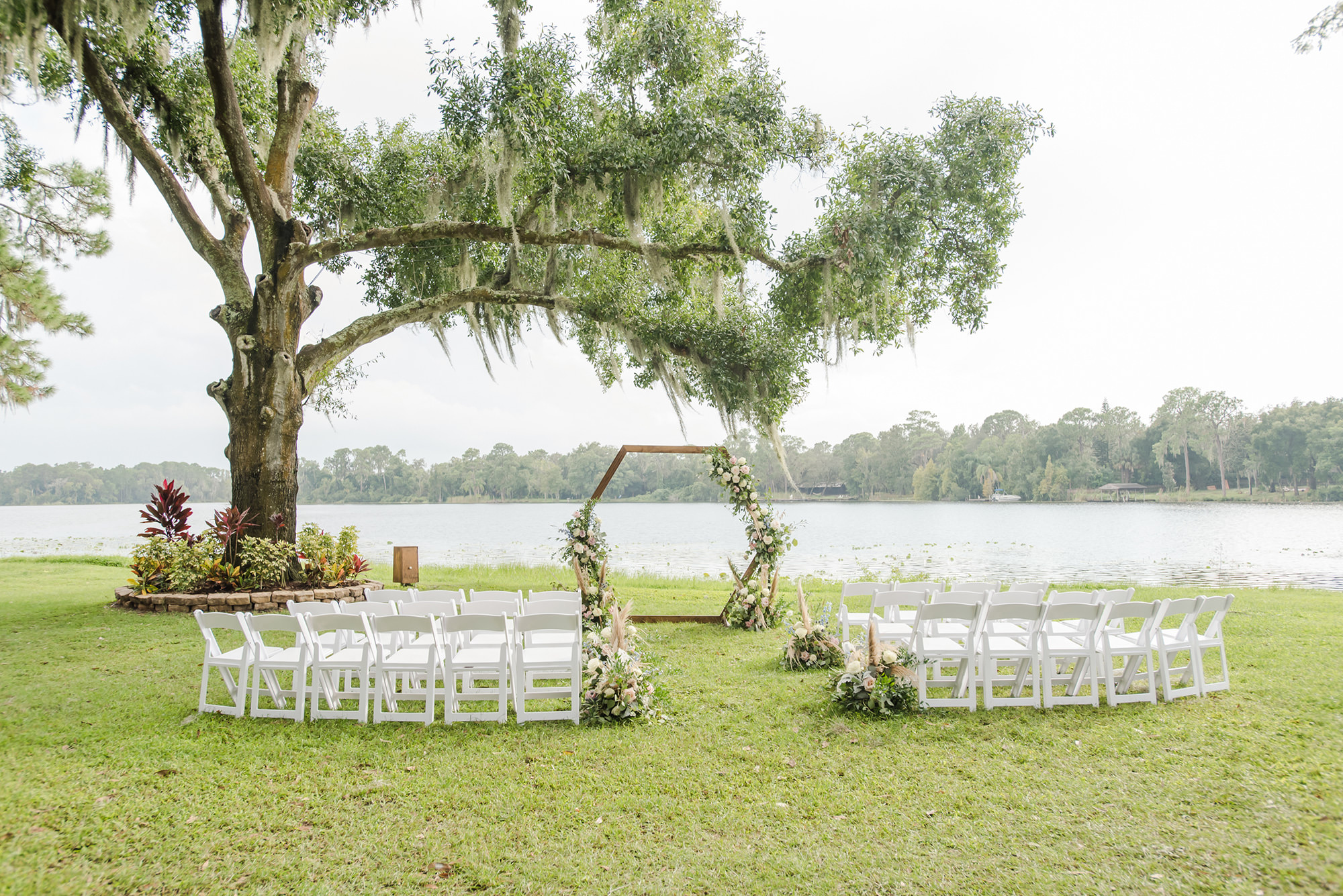 Florida Outdoor Waterfront Wedding Ceremony, Under Large Flowing Oak Tree, Rustic Wooden Hexagon Wedding Arch with Whimsical Inspired White and Dusty Rose and Pompous Grass Ceremony Flowers, White Chairs for Intimate Lakefront Ceremony   Tampa Bay Wedding Planner and Day of Coordinator Elegant Affairs by Design   Venue Barn at Crescent Lake