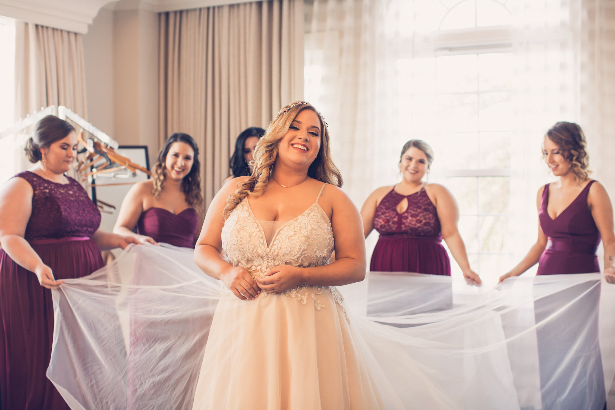 Tampa Bay Bride Getting Ready Wedding Portrait in Lace and Illusion V Neck Spaghetti Strap Bodice with Tulle Skirt, Bridesmaids in Burgundy Mix and Match Dresses | Wedding Photographer Luxe Light Images | St. Pete Wedding Hair and Makeup Michele Renee the Studio