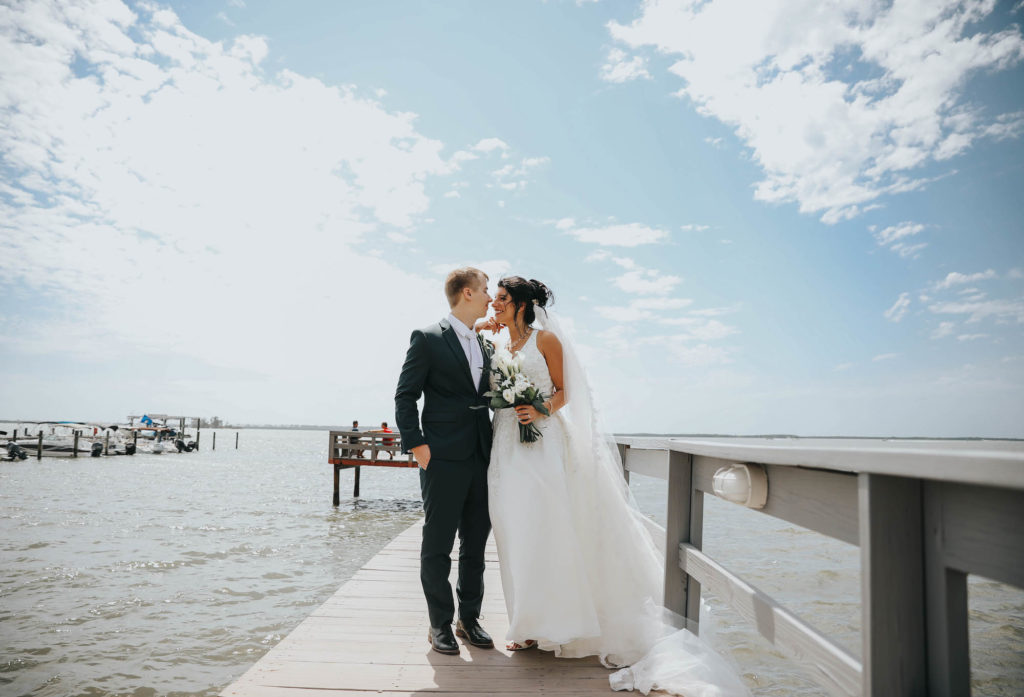 Florida Bride and Groom Wedding Portraits on Waterfront Private Pier in Dunedin, Holding Greenery Inspired Bridal Bouquet with White Flowers | Tampa Bay Wedding Florist Brides N Blooms | Clearwater Wedding Venue Beso Del Sol Resort