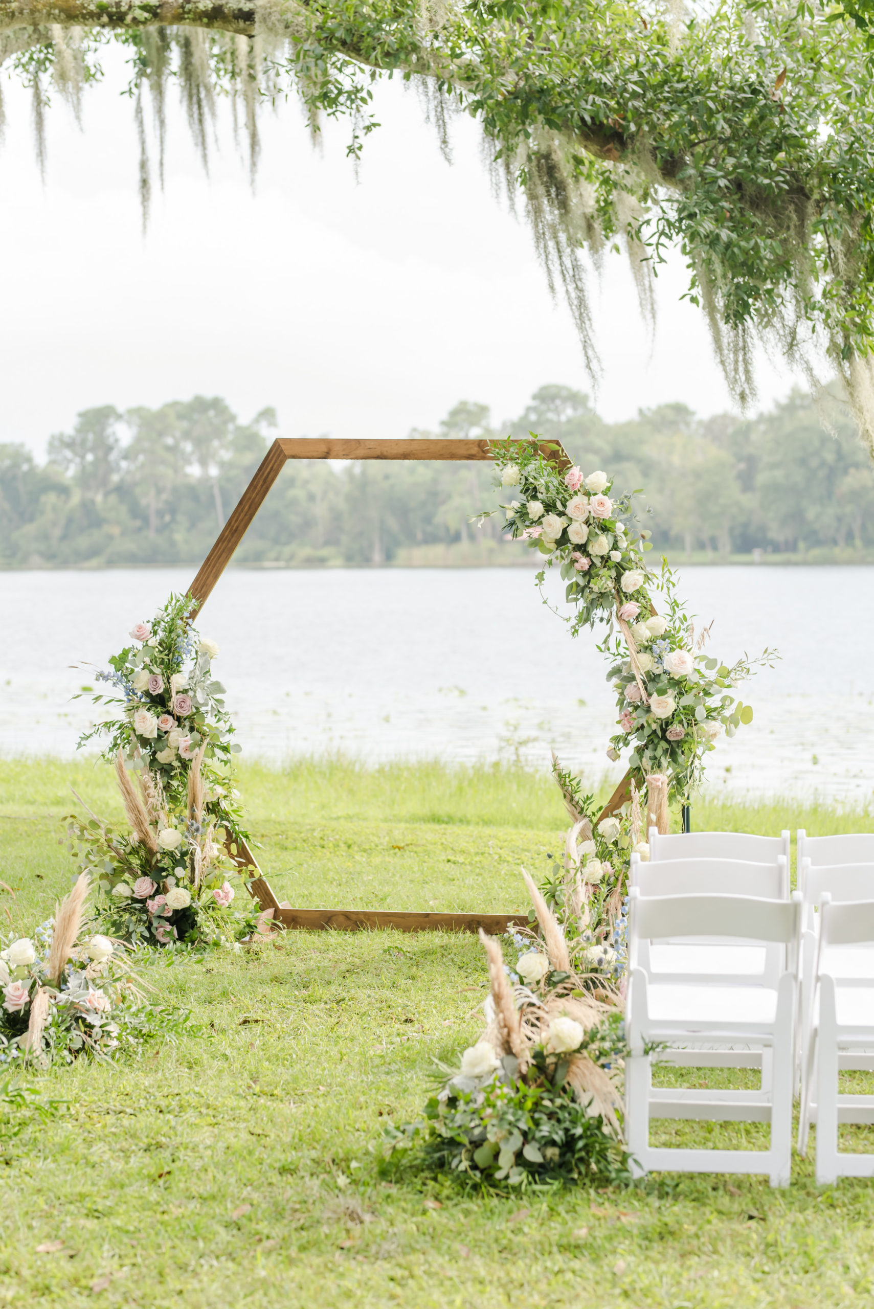 Florida Outdoor Waterfront Wedding Ceremony, Under Large Flowing Oak Tree, Rustic Wooden Hexagon Wedding Arch with Whimsical Inspired White and Dusty Rose Decor, and Pompous Grass Ceremony Flowers   Tampa Bay Wedding Planner and Day of Coordinator Elegant Affairs by Design